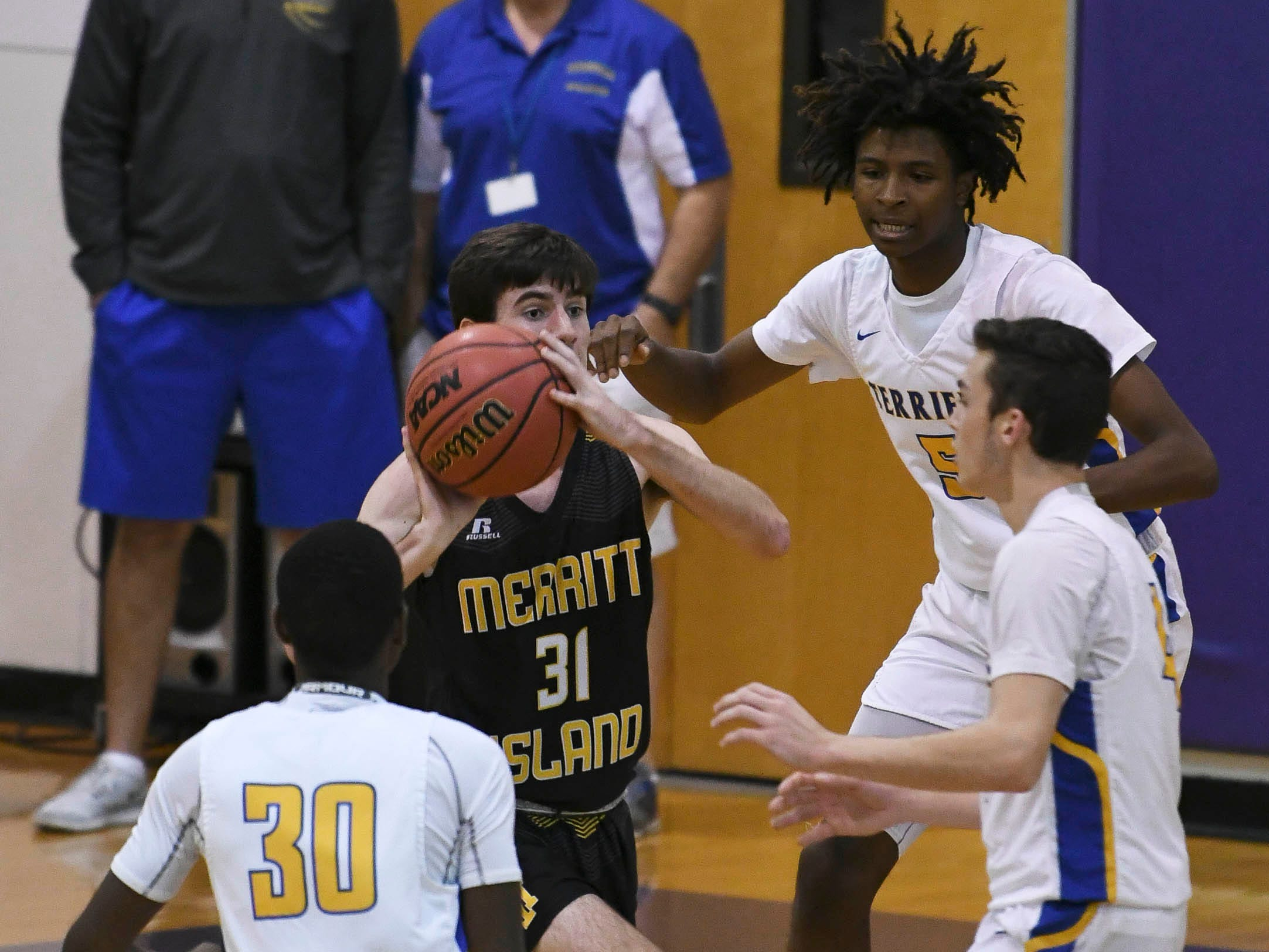 Hayden Wall of Merritt Island is surrounded by Titusville defenders during Tuesday's District 14-6A boys basketball tournament.