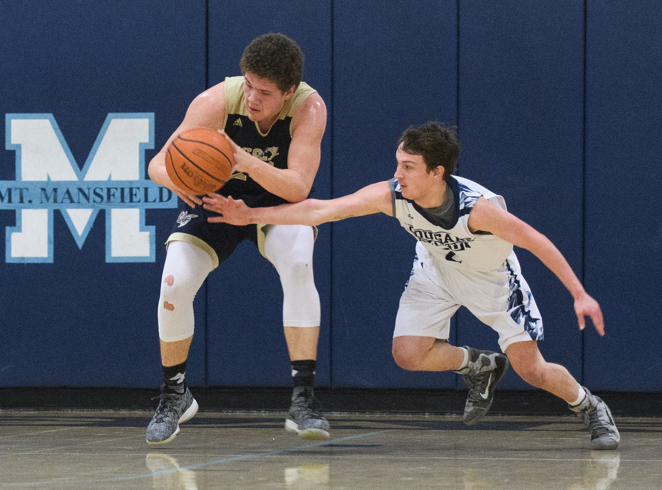MMU's Riley Smith (2) strips the ball from Essex's Anthony Decarvalho (23) during the boys basketball game between the Essex Hornets and the Mount Mansfield Cougars at MMU High School on Wednesday night February 13, 2019 in Jericho, Vermont.
