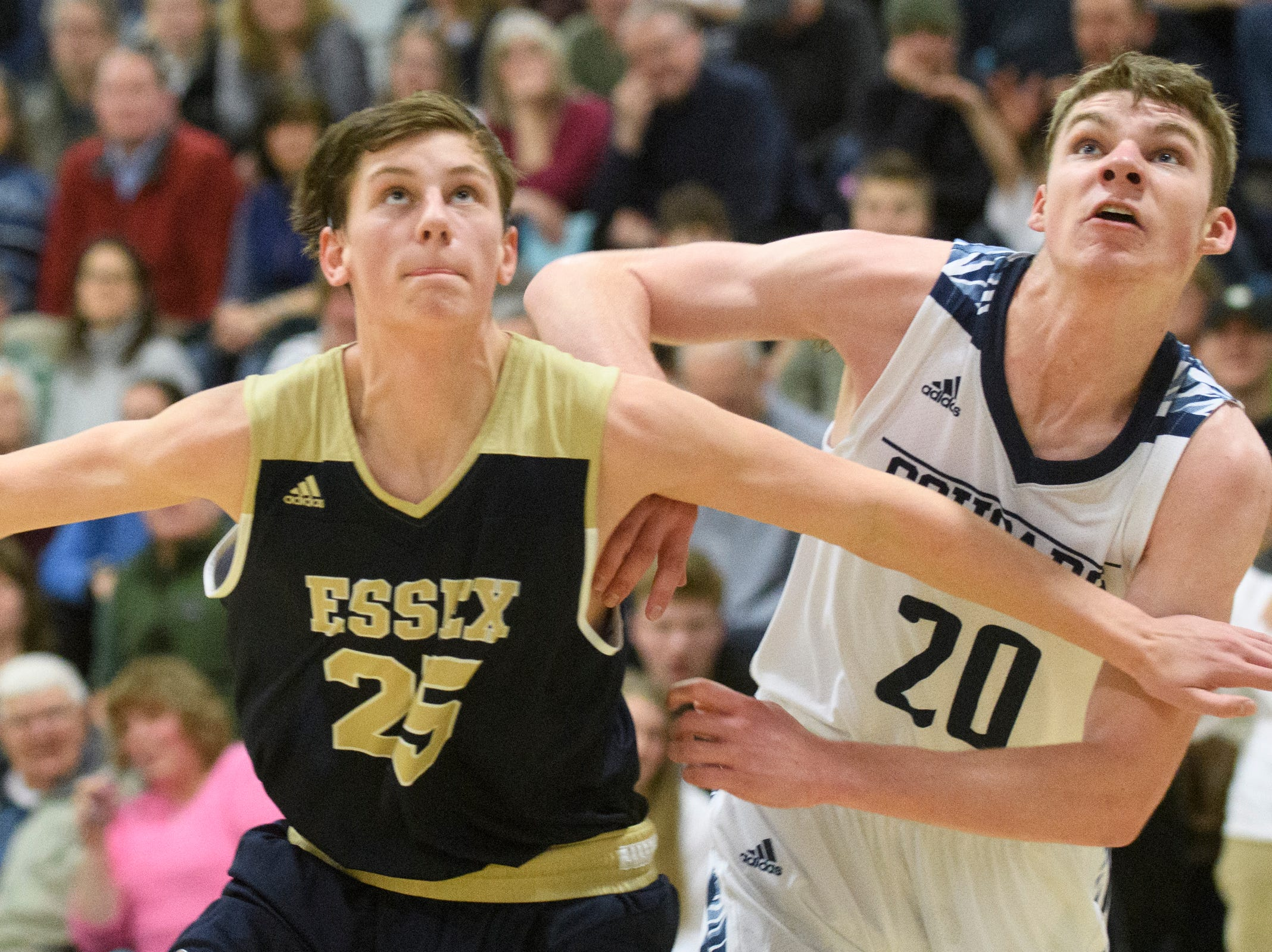 Essex's Mitchell Moffatt (25) and Connor Philbrick (20) battle for position on the free throw during the boys basketball game between the Essex Hornets and the Mount Mansfield Cougars at MMU High School on Wednesday night February 13, 2019 in Jericho, Vermont.