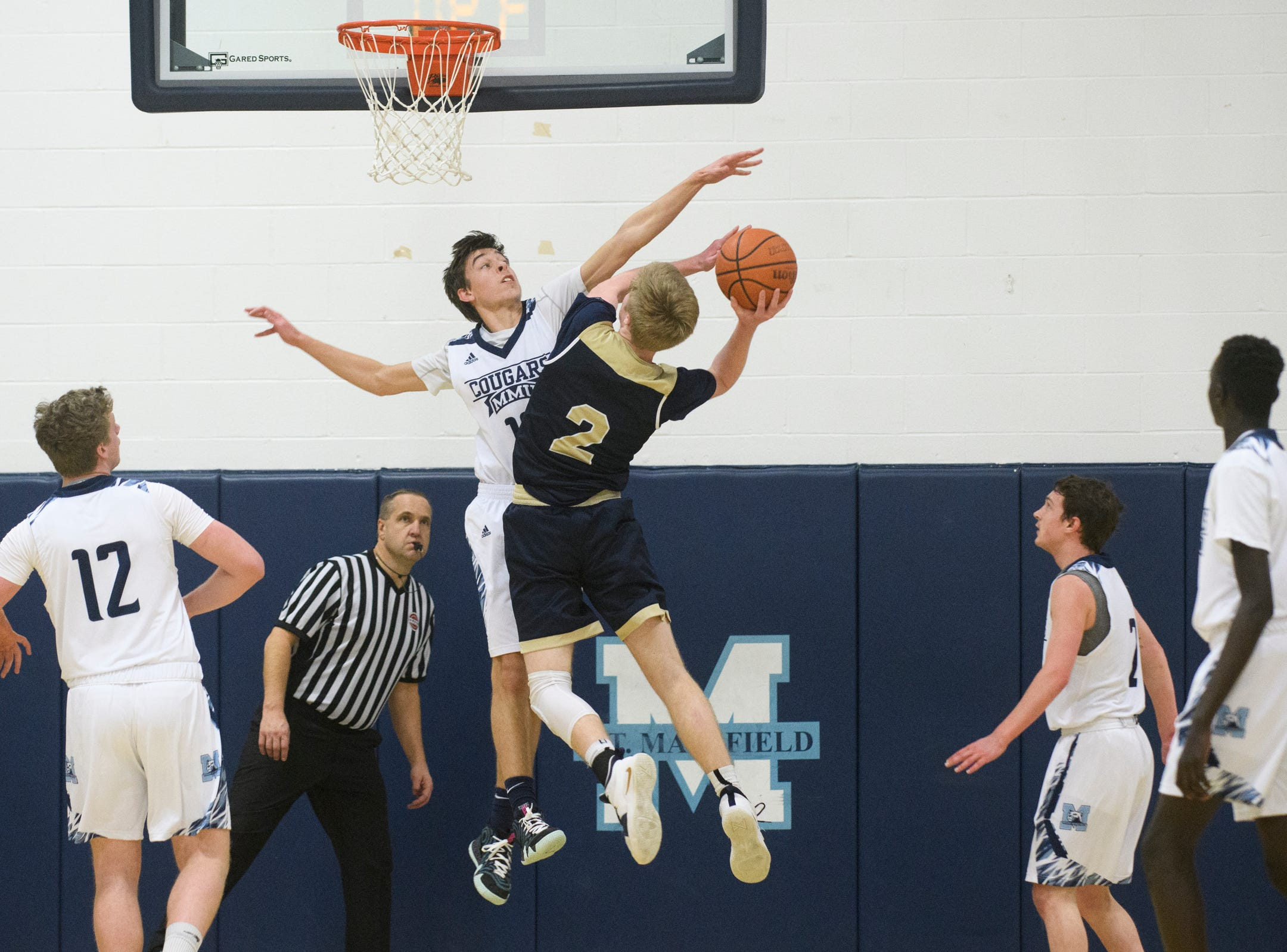 MMU's Becket Hill (13) blocks the shot by Essex's Stephen Astor (2) during the boys basketball game between the Essex Hornets and the Mount Mansfield Cougars at MMU High School on Wednesday night February 13, 2019 in Jericho, Vermont.