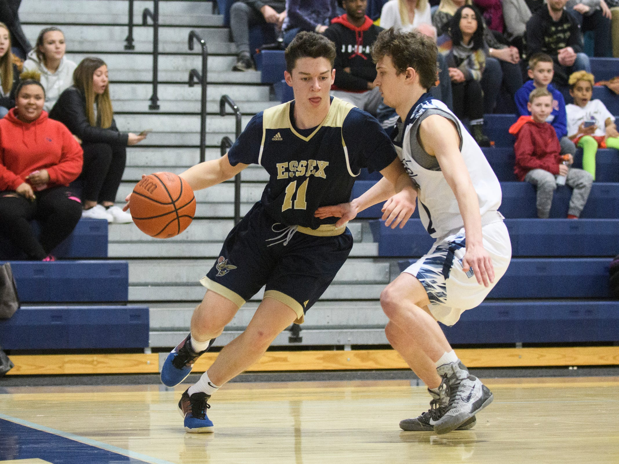Essex's Parker Whitney (11) drives to the hoop past MMU's Riley Smith (2) during the boys basketball game between the Essex Hornets and the Mount Mansfield Cougars at MMU High School on Wednesday night February 13, 2019 in Jericho, Vermont.