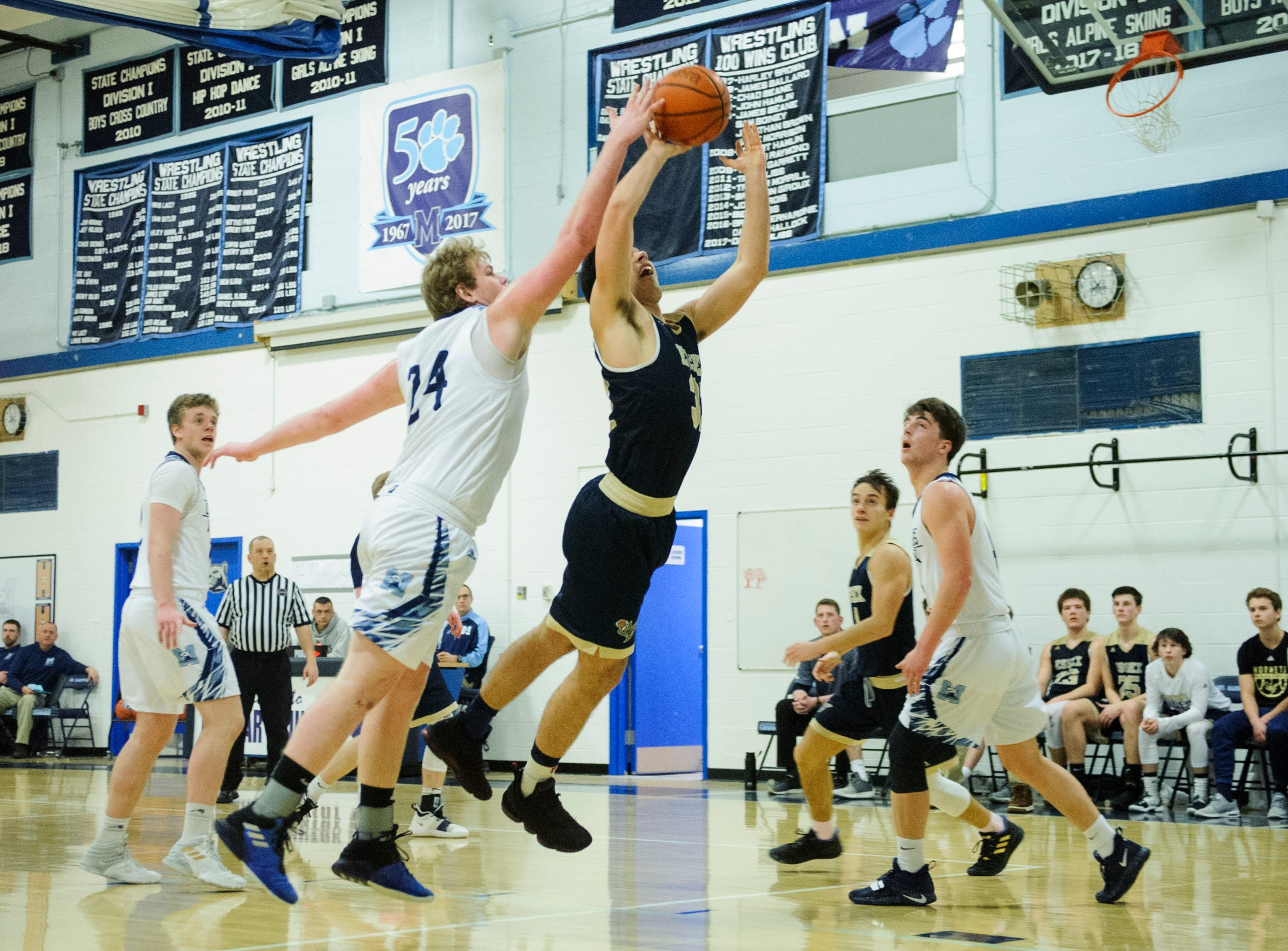 MMU's Mark Howland (24) blocks the shot by Essex's Adin Peco (32) during the boys basketball game between the Essex Hornets and the Mount Mansfield Cougars at MMU High School on Wednesday night February 13, 2019 in Jericho, Vermont.
