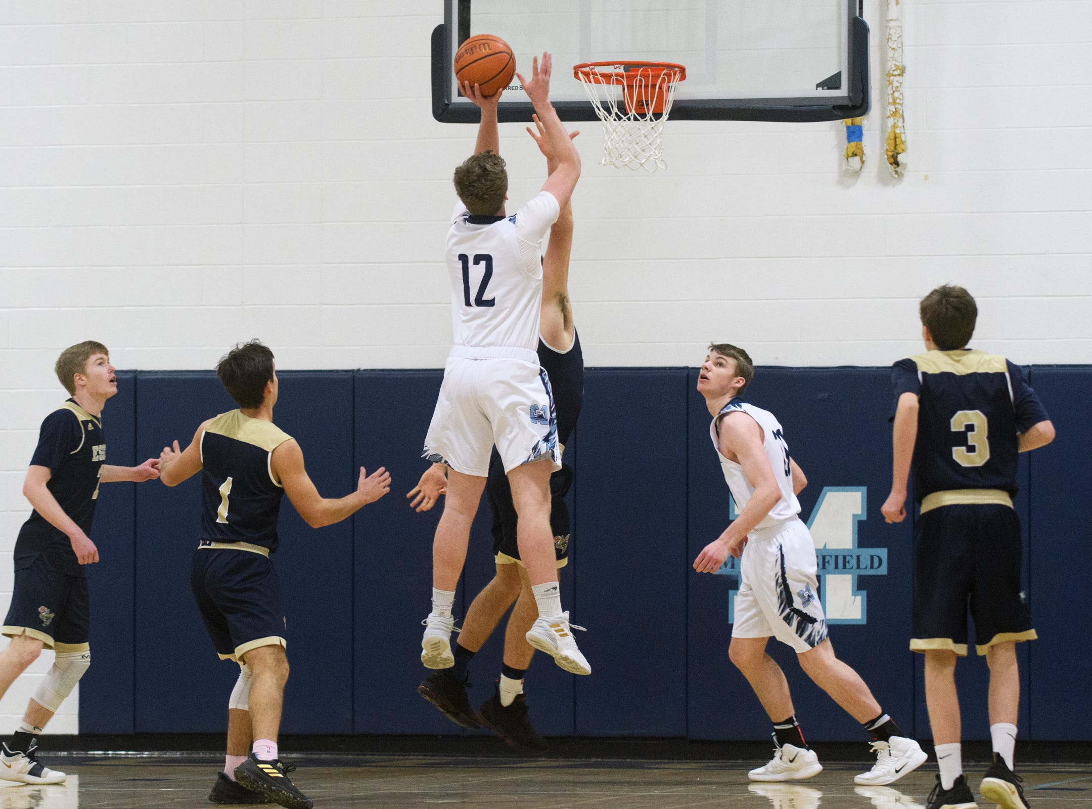 MMU's Asa Carlson (12) shoots the ball during the boys basketball game between the Essex Hornets and the Mount Mansfield Cougars at MMU High School on Wednesday night February 13, 2019 in Jericho, Vermont.