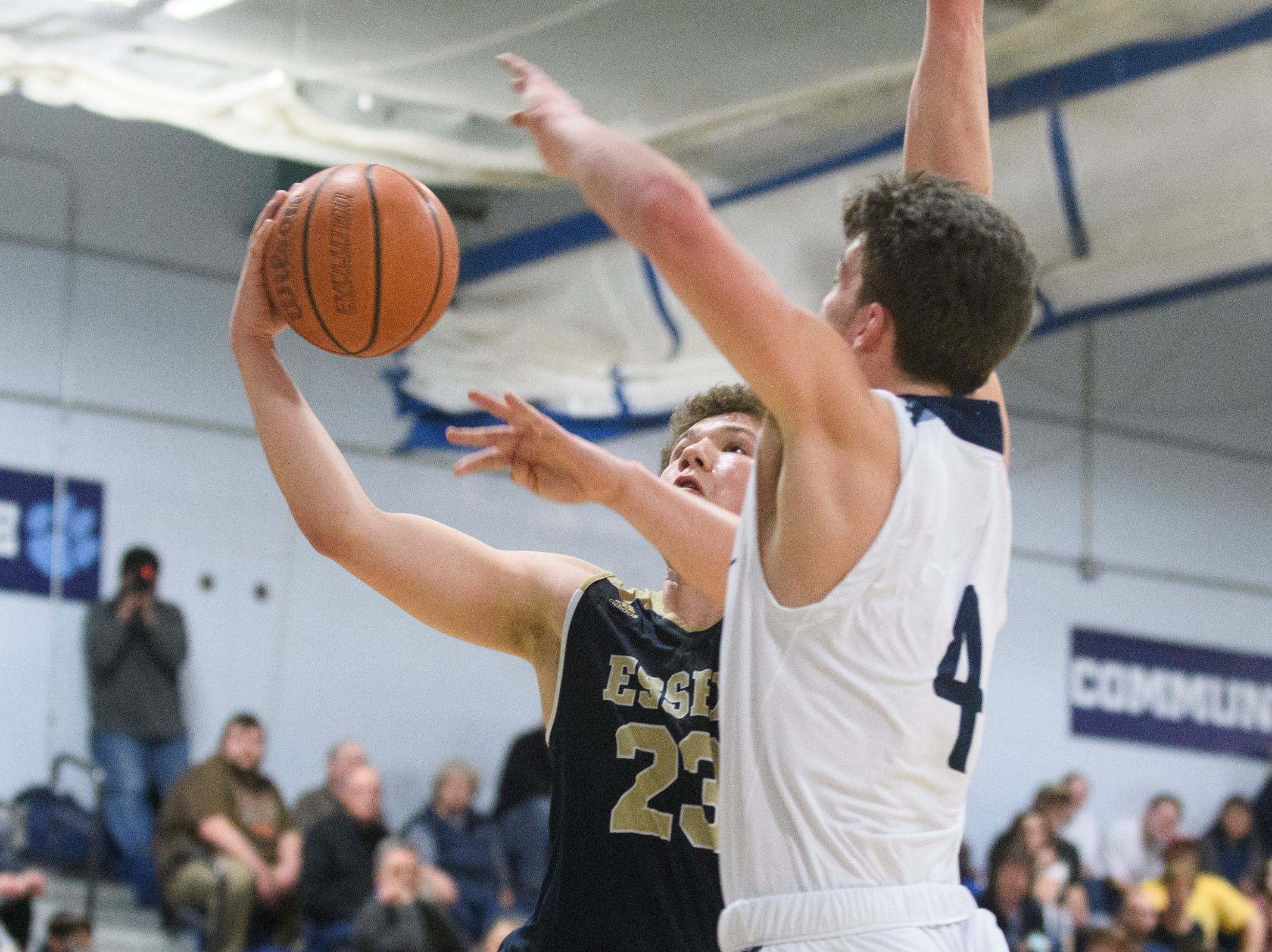 Essex's Anthony Decarvalho (23) leaps past MMU's Harrison Leombruno-Nicholson (4) for a lay up during the boys basketball game between the Essex Hornets and the Mount Mansfield Cougars at MMU High School on Wednesday night February 13, 2019 in Jericho, Vermont.