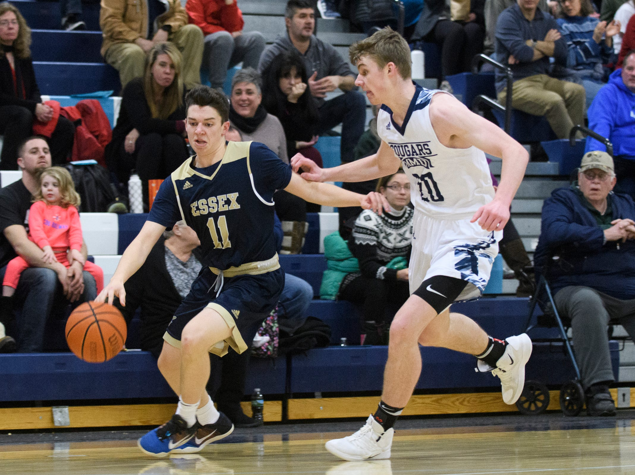 Essex's Parker Whitney (11) dribbles the ball past MMU's Connor Philbrick (20) during the boys basketball game between the Essex Hornets and the Mount Mansfield Cougars at MMU High School on Wednesday night February 13, 2019 in Jericho, Vermont.