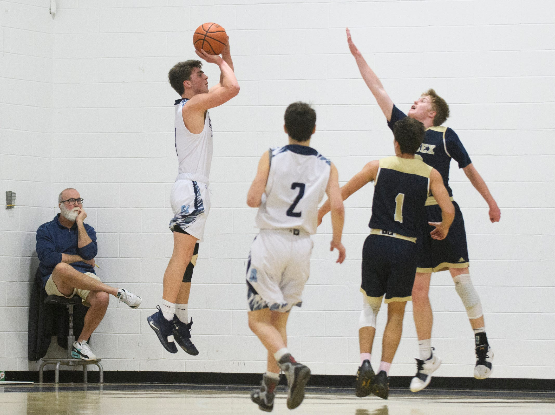 MMU's Harrison Leombruno-Nichlson (4) shoots a three pointer during the boys basketball game between the Essex Hornets and the Mount Mansfield Cougars at MMU High School on Wednesday night February 13, 2019 in Jericho, Vermont.