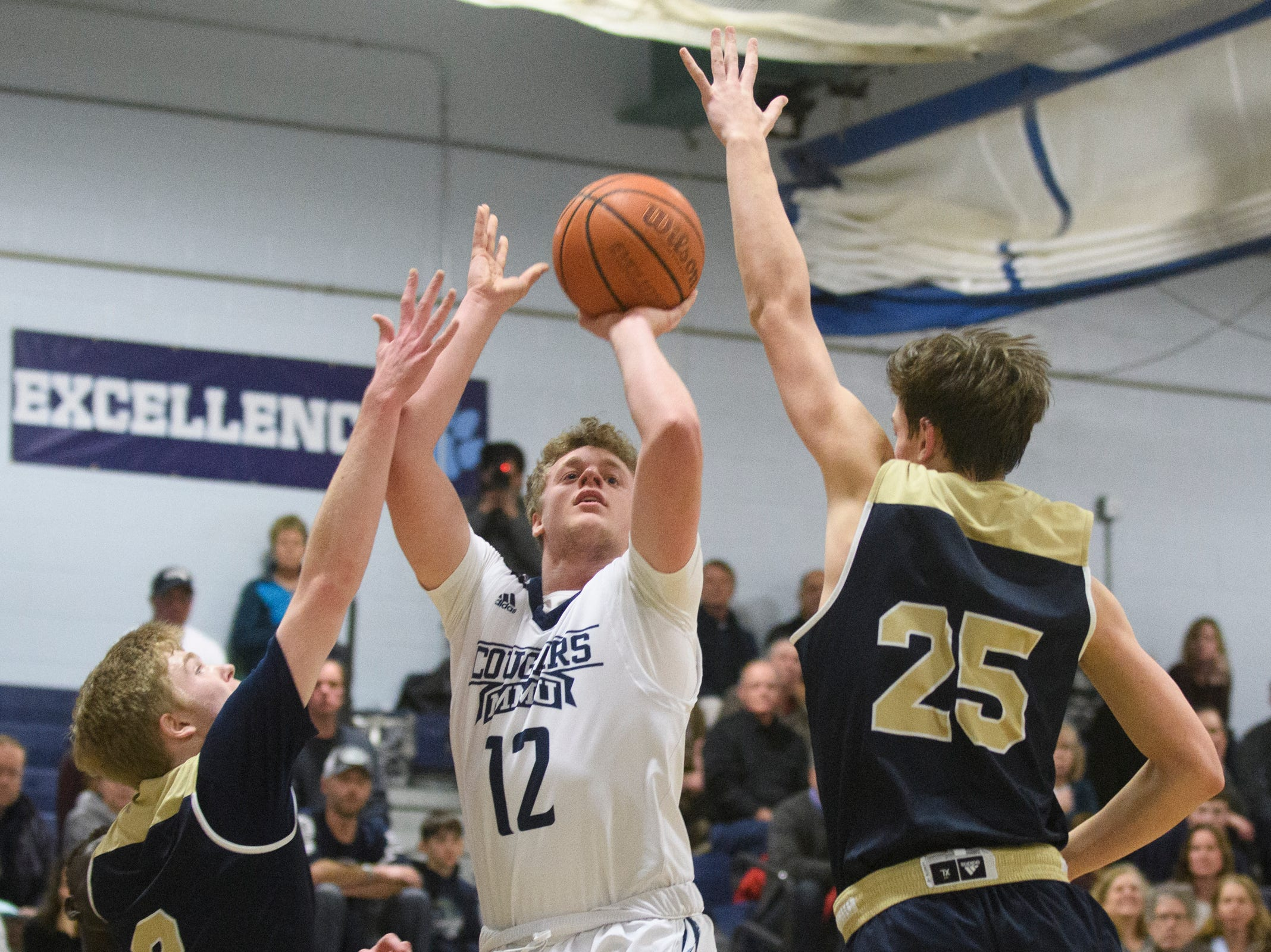 MMU's Asa Carlson (12) takes a shot over Essex's Mitchell Moffatt (25) during the boys basketball game between the Essex Hornets and the Mount Mansfield Cougars at MMU High School on Wednesday night February 13, 2019 in Jericho, Vermont.