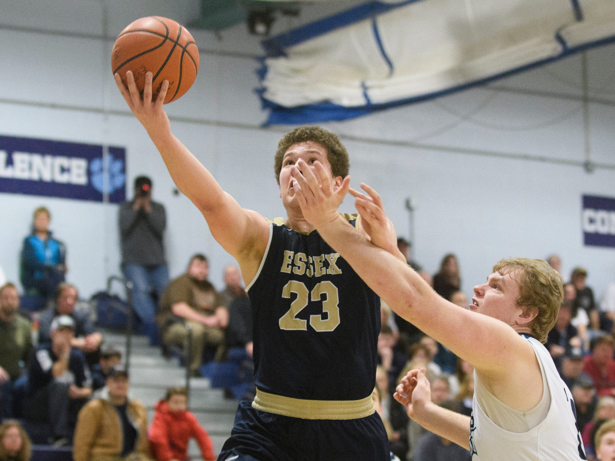 Essex's Anthony Decarvalho (23) leaps past MMU's Mark Howland (24) for a lay up during the boys basketball game between the Essex Hornets and the Mount Mansfield Cougars at MMU High School on Wednesday night February 13, 2019 in Jericho, Vermont.