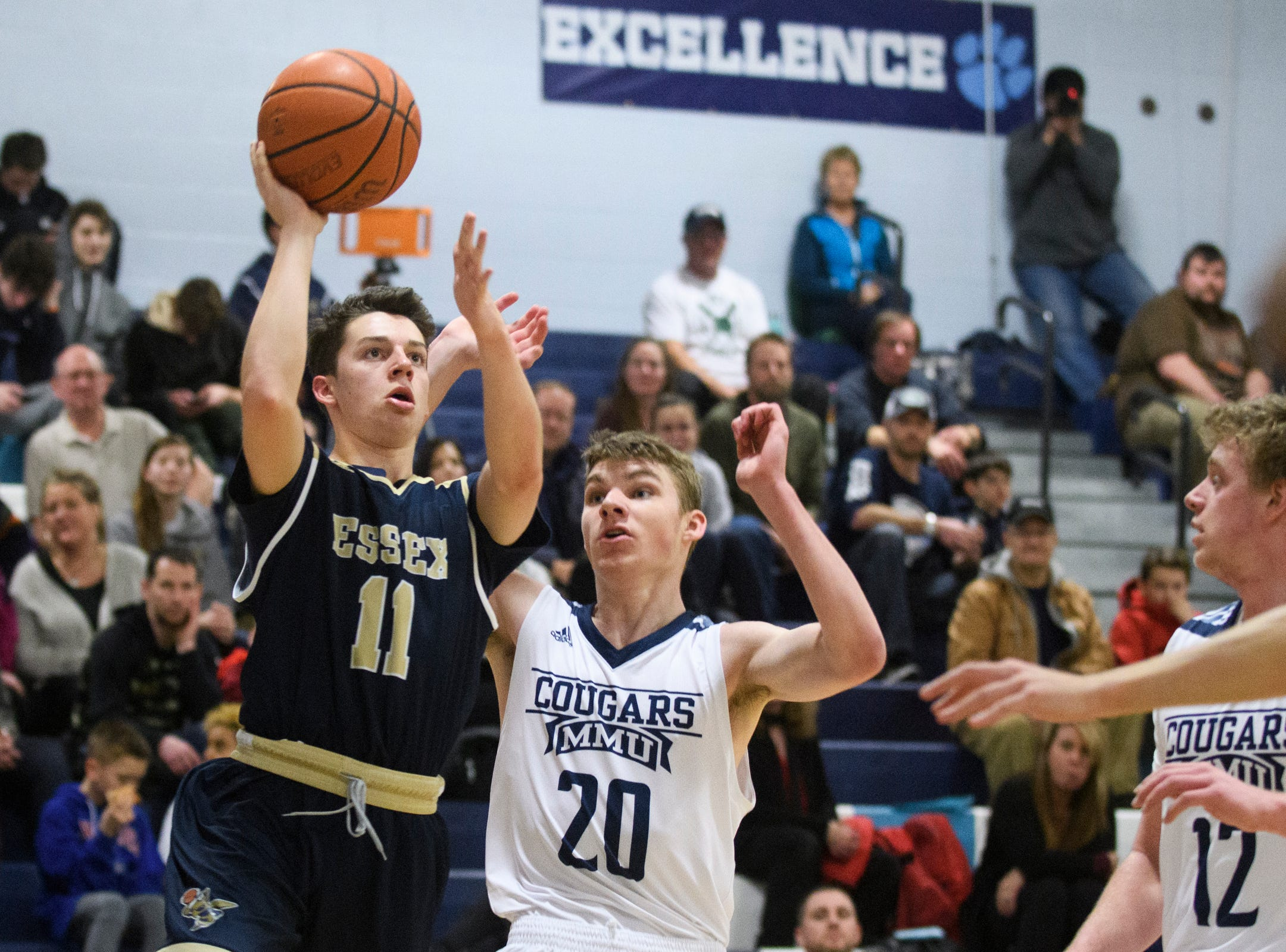 Essex's Parker Whitney (11) leaps past MMU's Connor Philbrick (20) for a lay up during the boys basketball game between the Essex Hornets and the Mount Mansfield Cougars at MMU High School on Wednesday night February 13, 2019 in Jericho, Vermont.