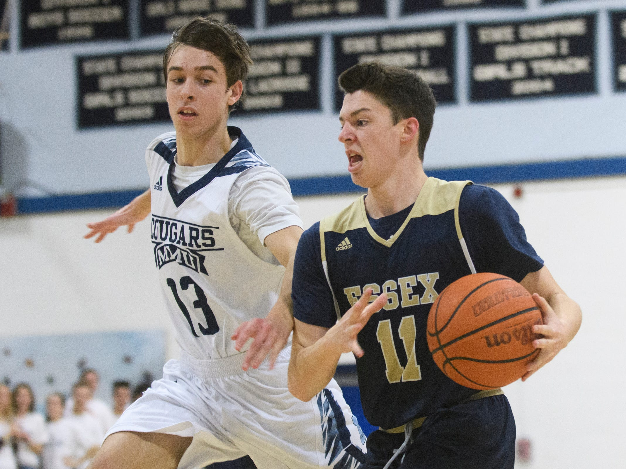 Essex's Parker Whitney (11) drives to the hoop past MMU's Becket Hill (13) during the boys basketball game between the Essex Hornets and the Mount Mansfield Cougars at MMU High School on Wednesday night February 13, 2019 in Jericho, Vermont.