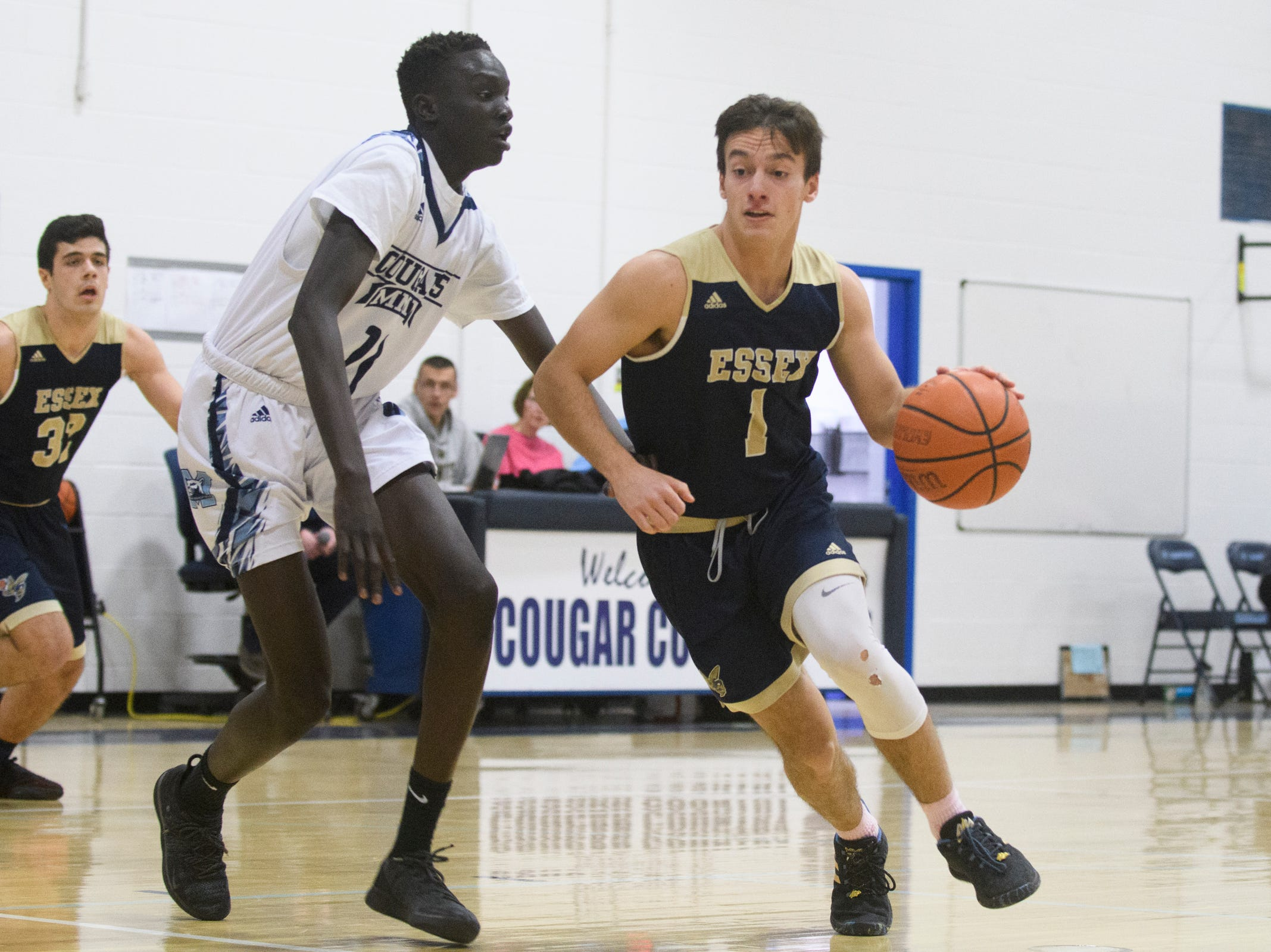 Essex's Robbie Meslin (1) drives to the hoop past MMU's Taylor Bowen (11) during the boys basketball game between the Essex Hornets and the Mount Mansfield Cougars at MMU High School on Wednesday night February 13, 2019 in Jericho, Vermont.