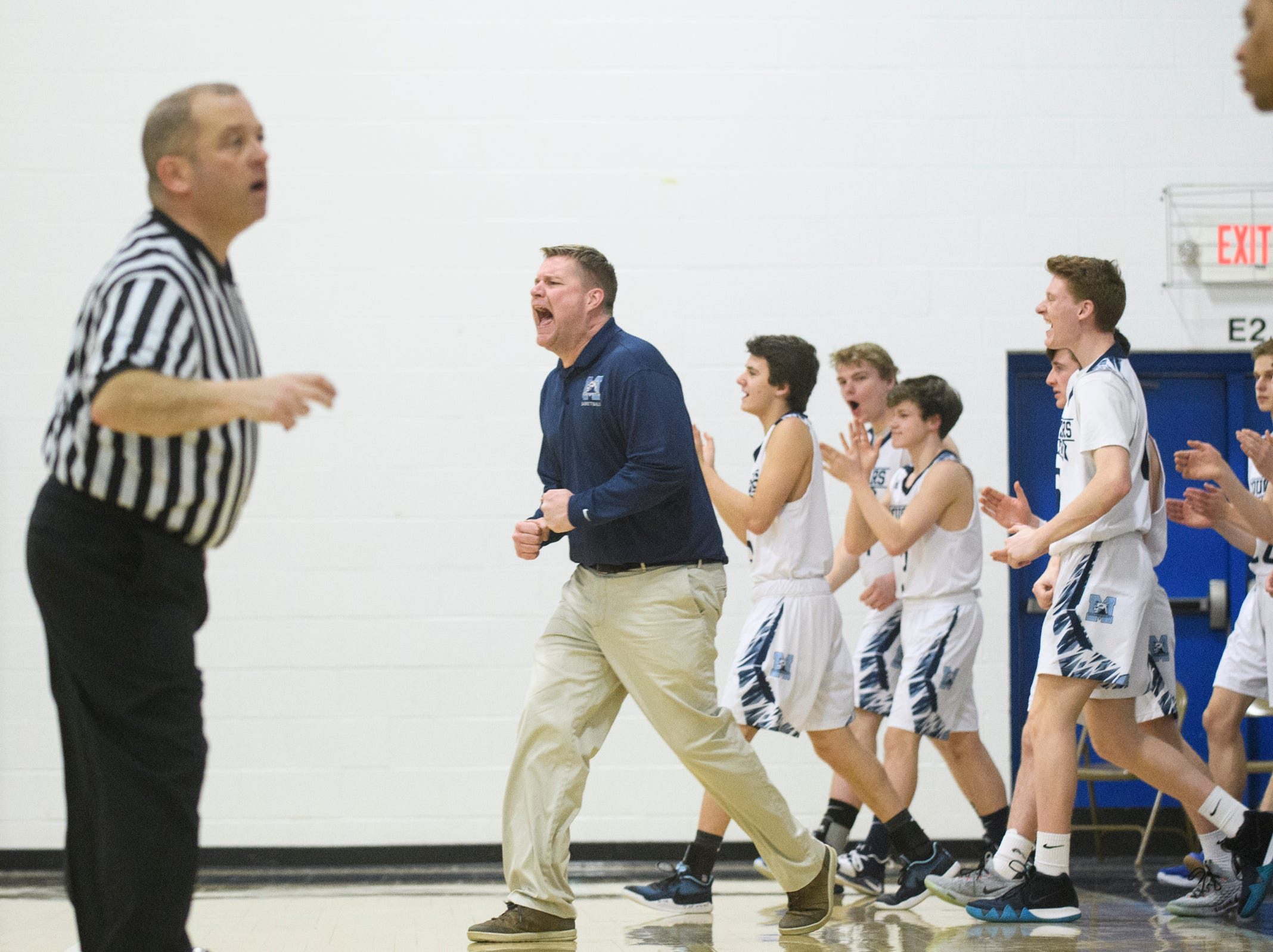 MMU head coach Jeff Davis cheers as Essex calls a time out during the boys basketball game between the Essex Hornets and the Mount Mansfield Cougars at MMU High School on Wednesday night February 13, 2019 in Jericho, Vermont.