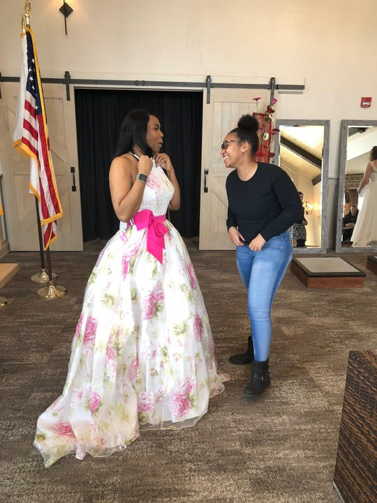 Danita Hunt and her daughter Azaria, 18, share a laugh as Danita shops for a bridal gown at the Camden County Veterans Dress Giveaway.