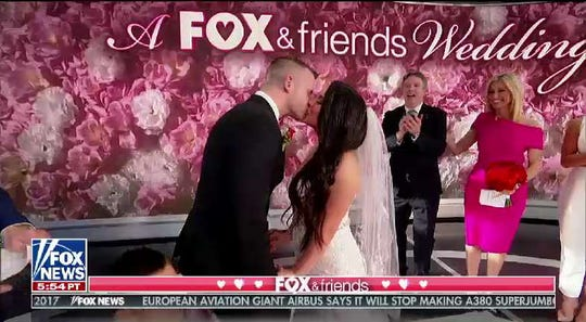 Joseph Muller Jr., a Millville police officer, kisses Priscilla Pazmino, an Air Force medic, as they are married on 'FOX & Friends' on Valentine's Day.