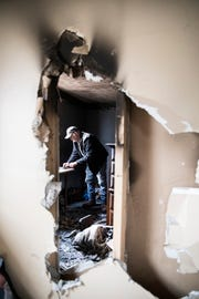 Dave Gravle sifts through debris in the room belonging to his brother Thursday afternoon after a morning fire at 642 Pine St. sent his brother Dan Chaney, his mother Joyce Chaney, and police officer Chris McGowan to the hospital.