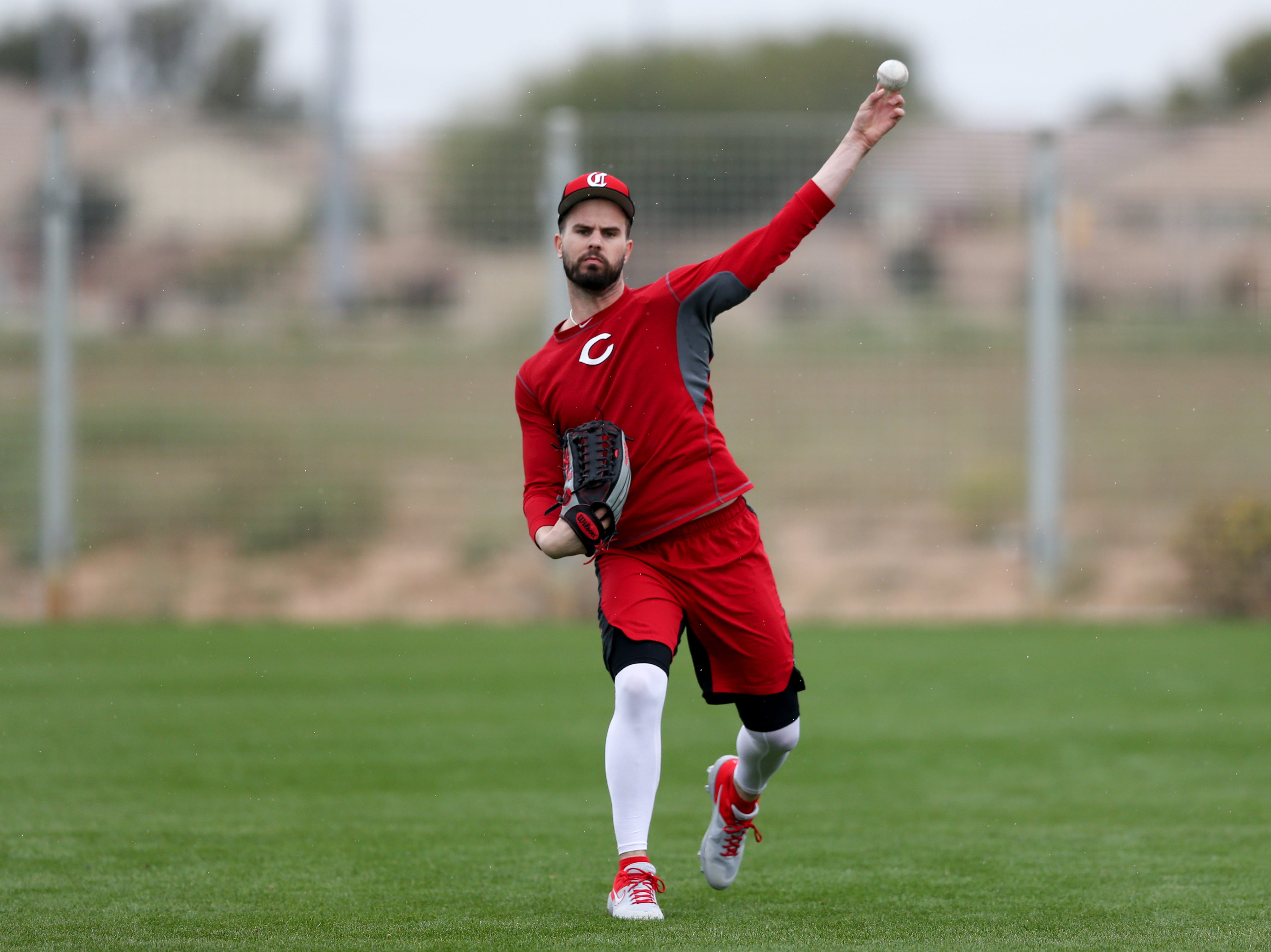 Cincinnati Reds right fielder Jesse Winker (33) tosses the ball with Cincinnati Reds outfielder Matt Kemp (27) (not pictured), as pitchers and catchers work out, Thursday, Feb. 14, 2019, at the Cincinnati Reds spring training facility in Goodyear, Arizona.