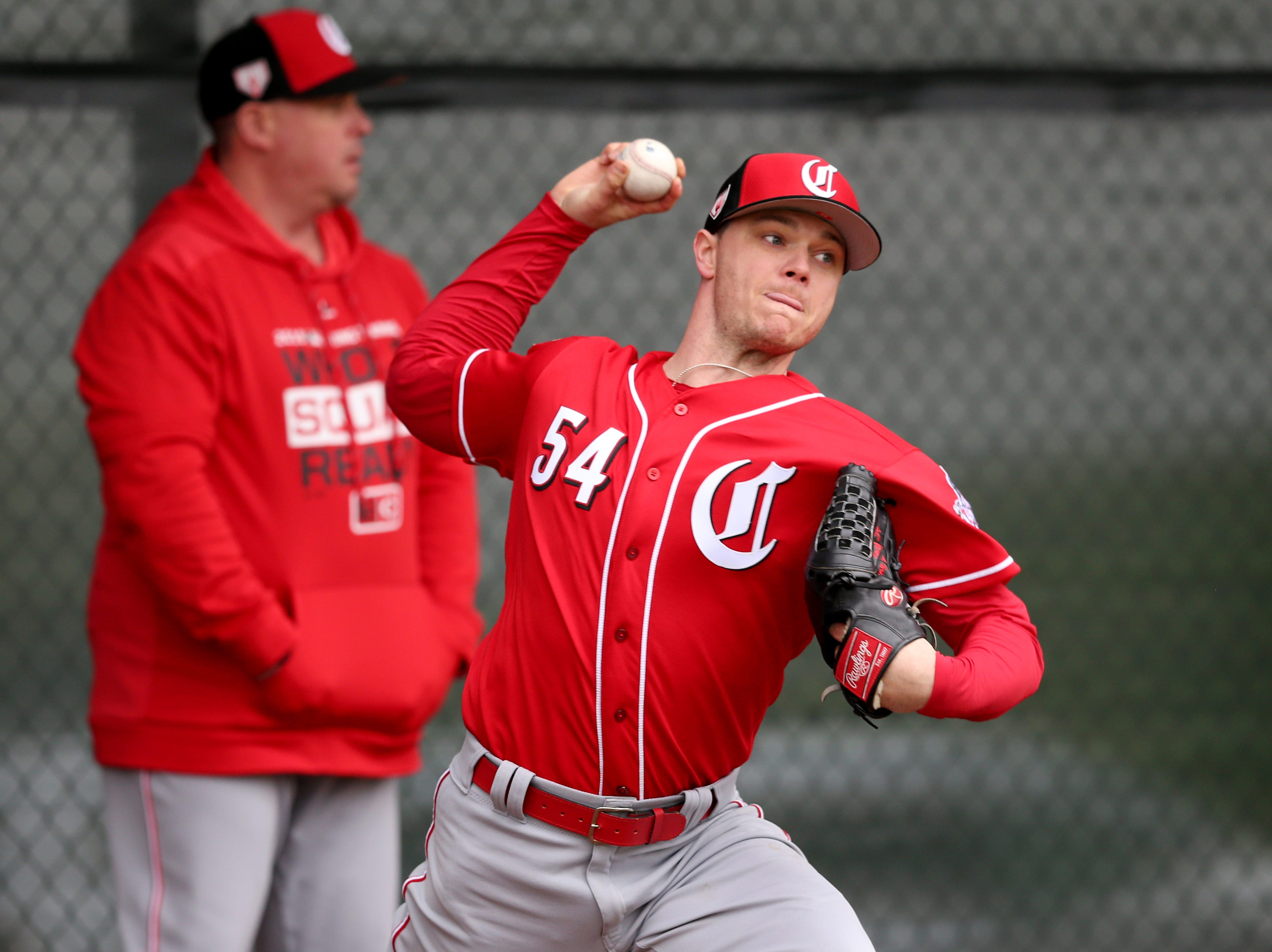 Cincinnati Reds starting pitcher Sonny Gray (54) delivers during a bullpen session as pitching coach Derek Johnson stands in the background, Thursday, Feb. 14, 2019, at the Cincinnati Reds spring training facility in Goodyear, Arizona.