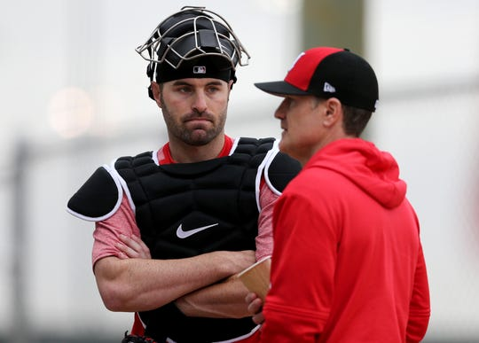 Cincinnati Reds catcher Curt Casali (12), left, talks with Cincinnati Reds manager David Bell (25), Thursday, Feb. 14, 2019, at the Cincinnati Reds spring training facility in Goodyear, Arizona.
