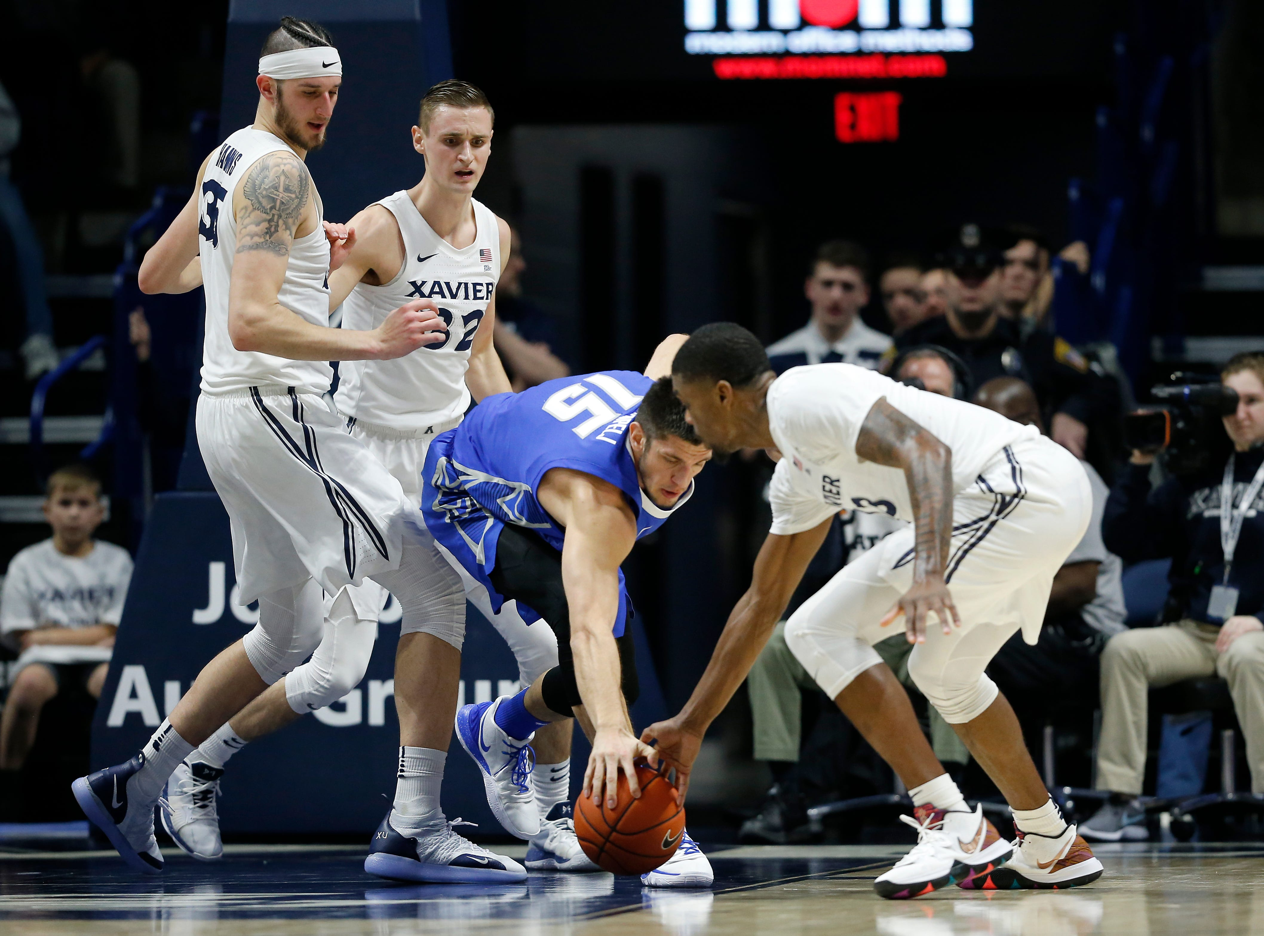 Creighton Bluejays forward Martin Krampelj (15) and Xavier Musketeers forward Naji Marshall (13) reach for a loose ball in the first half of the NCAA Big East Conference basketball game between the Xavier Musketeers and the Creighton Bluejays at Xavier's Cintas Center in Cincinnati on Wednesday, Feb. 13, 2019. Xavier led 36-30 at halftime.