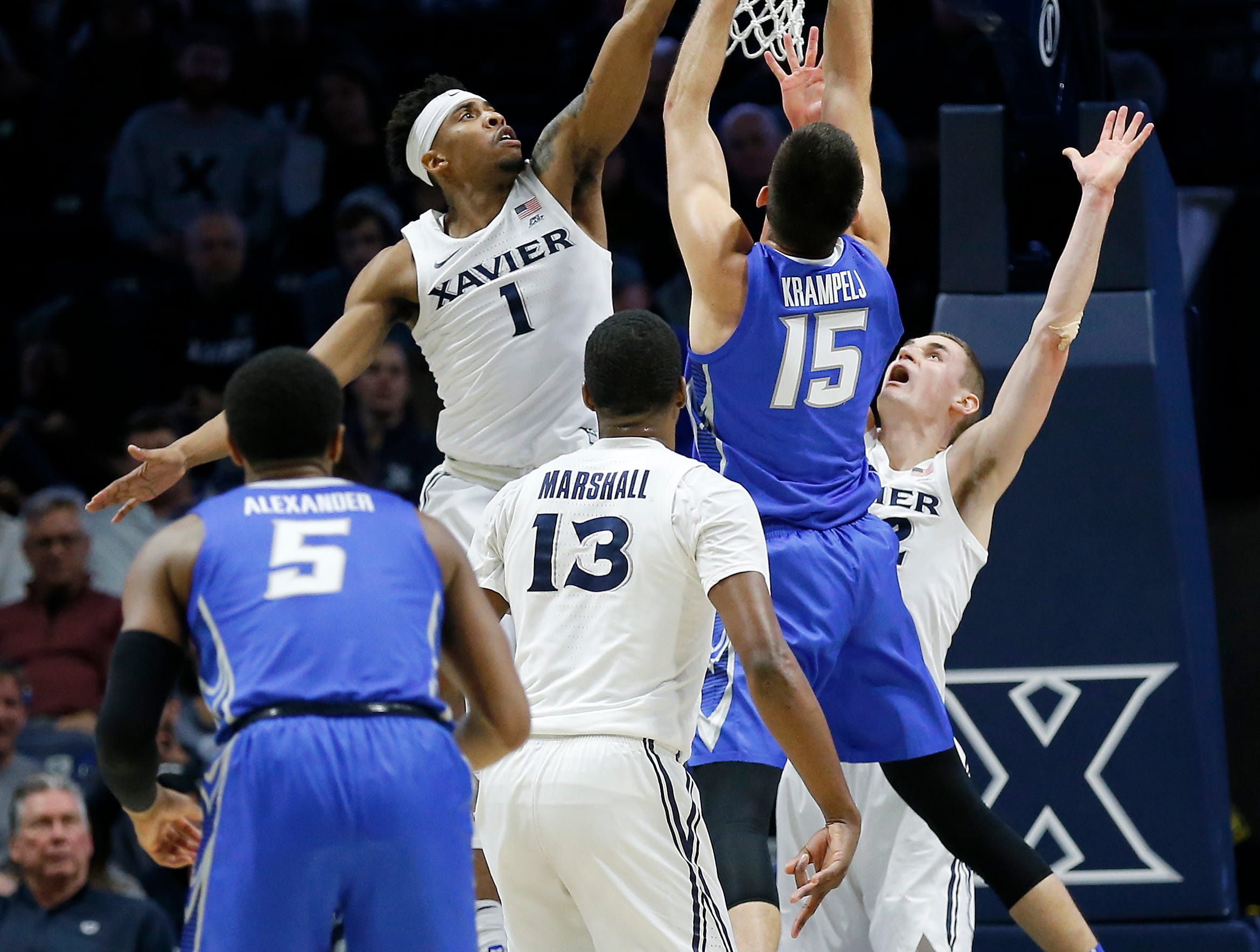 Xavier Musketeers guard Paul Scruggs (1) stretches to block a shot by Creighton Bluejays forward Martin Krampelj (15) in the first half of the NCAA Big East Conference basketball game between the Xavier Musketeers and the Creighton Bluejays at Xavier's Cintas Center in Cincinnati on Wednesday, Feb. 13, 2019. Xavier led 36-30 at halftime.