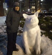 Anne Robinson stands next to a snow sculpture of a pig she created, honoring her Iowa roots and celebrating the Chinese Year of the Pig in Seattle's Chinese-International District.