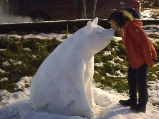 A young girl kisses the nose of the snow pig sculpted by Anne Robinson in Seattle's Chinese-International District.