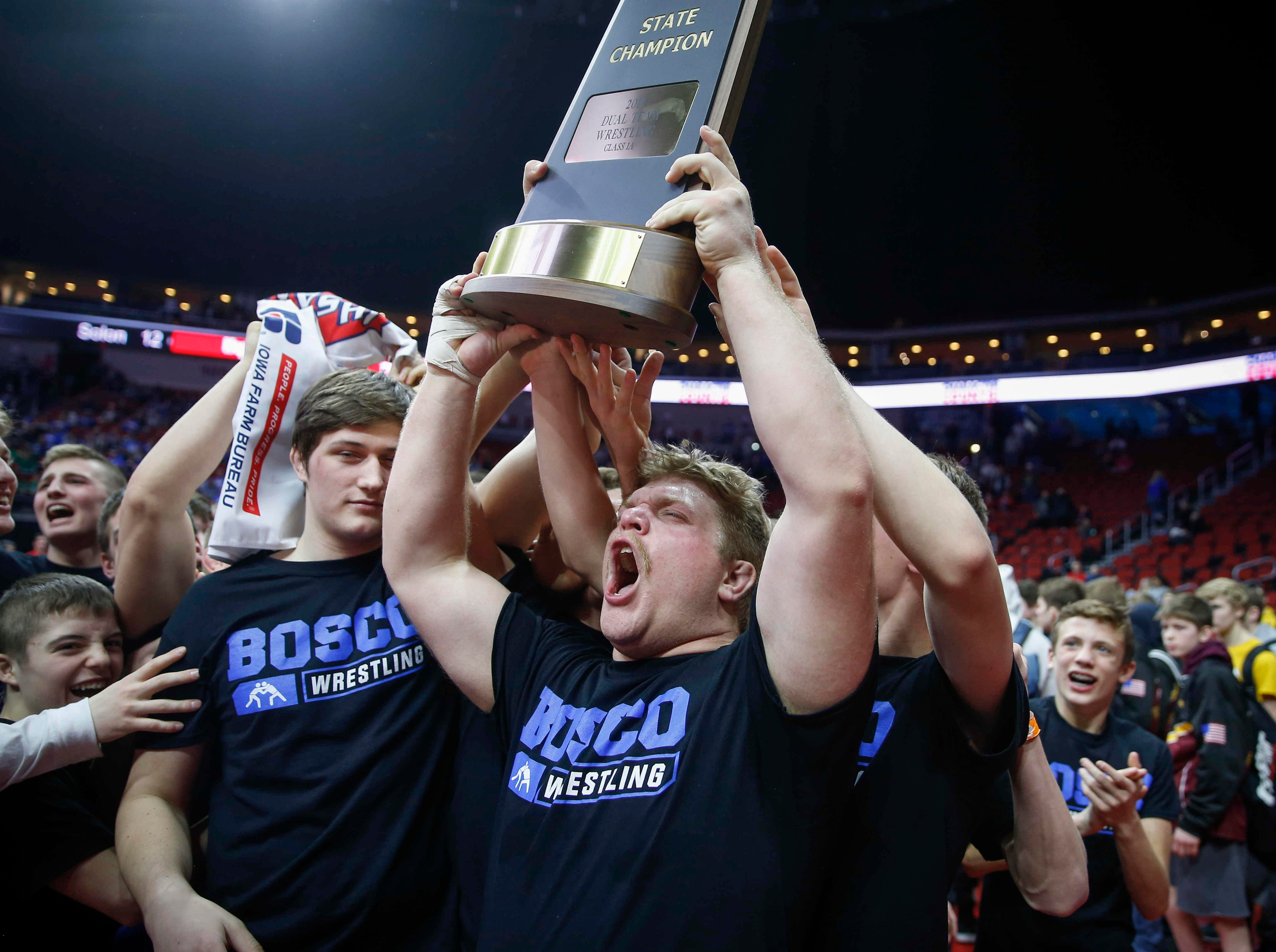 Members of the Don Bosco wrestling team raise the Class 1A state championship trophy during the 2019 Iowa high school dual wrestling state tournament on Wednesday, Feb. 13, 2019, at Wells Fargo Arena in Des Moines.