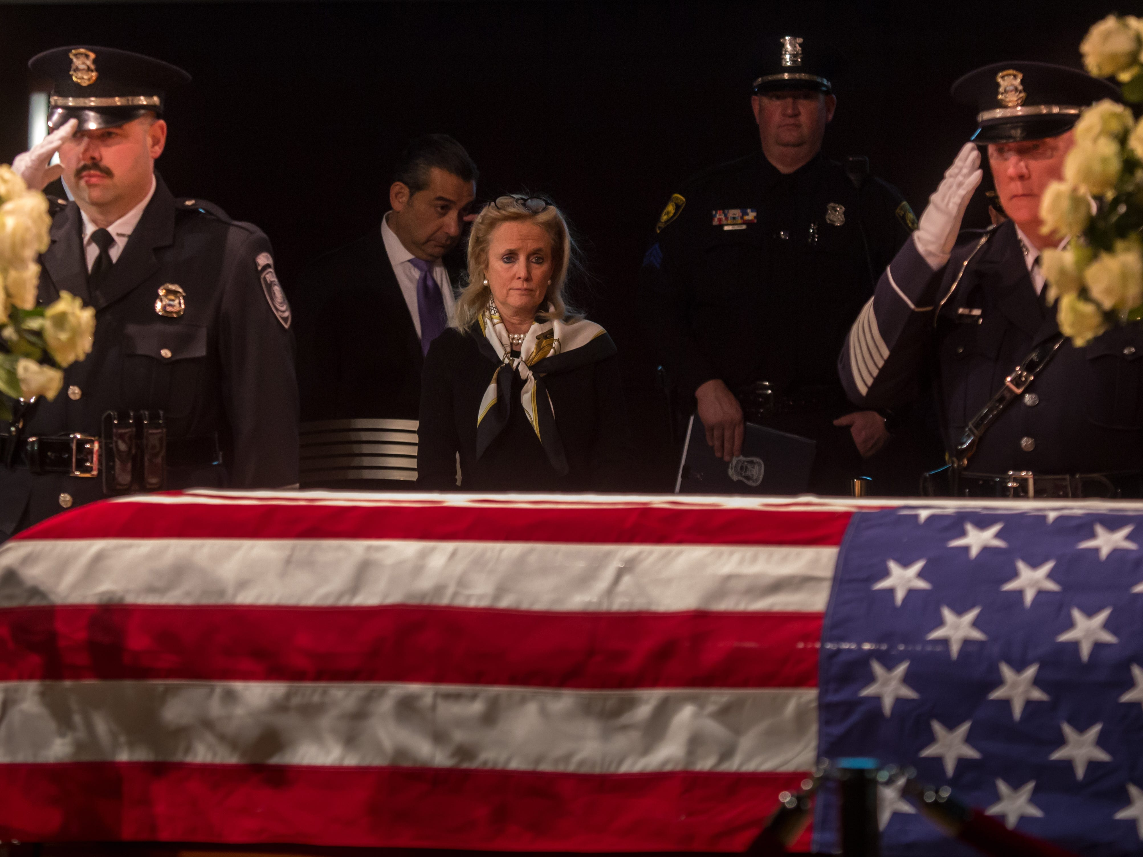 Rep. Debbie Dingell stands by the casket of her late husband former US Representative John D. Dingell during his visitation at the Ford Community and Performing Arts Center in Dearborn on Monday, February 11, 2019.
