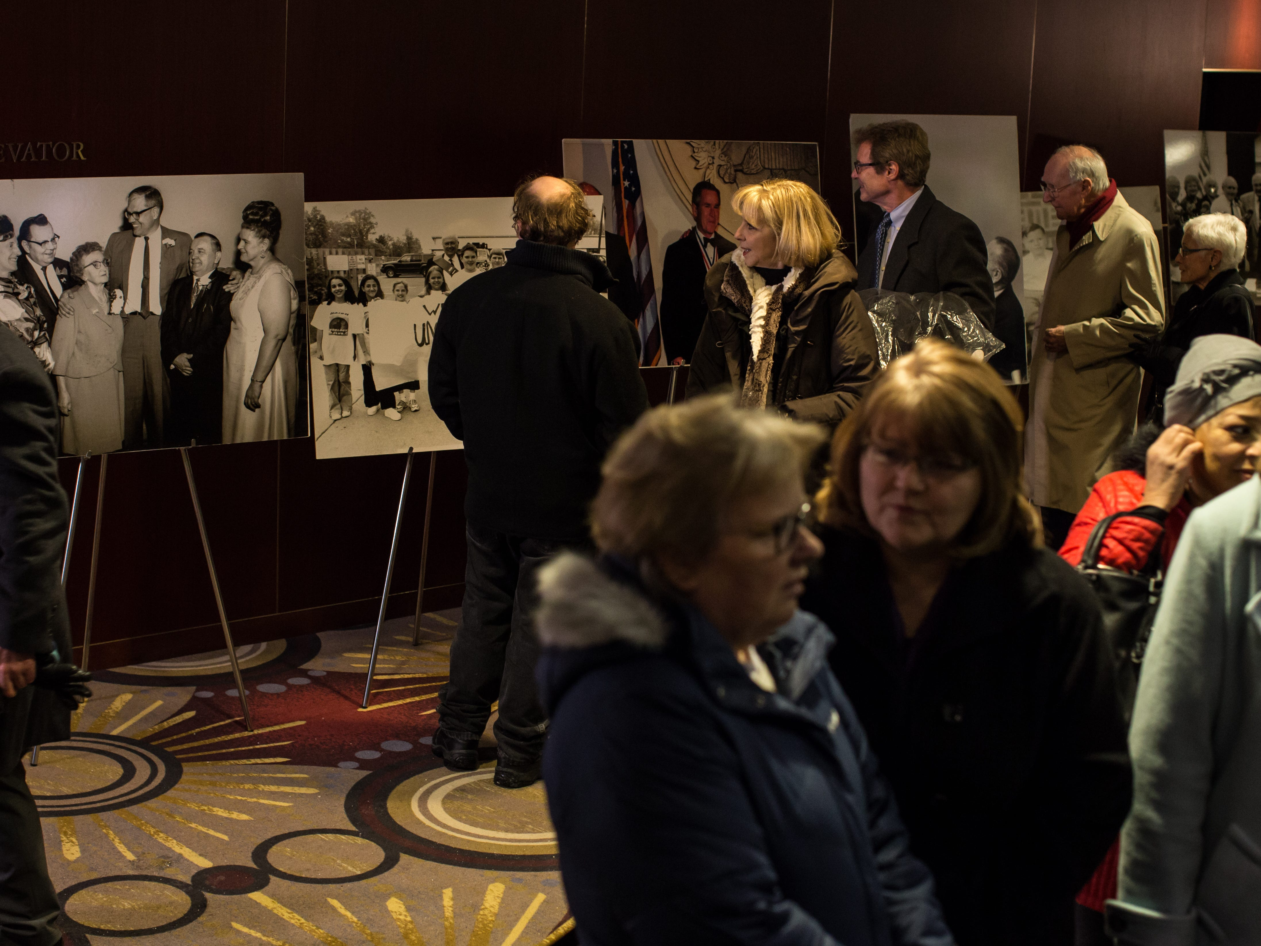 People look over old photos after paying their respects during the visitation for the former US Representative John D. Dingell at the Ford Community and Performing Arts Center in Dearborn on Monday, February 11, 2019.
