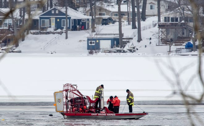 Authorities search for a snowmobiler, Thursday, Feb. 14, 2019, in Spencer Township, Mich. Authorities say a snowmobiler is missing at a lake in western Michigan and another snowmobiler was rescued from unstable ice at the lake. The Kent County sheriff's office responded Wednesday night to Lincoln Lake in Spencer Township following a 911 call from a person who reported he was riding with a man who apparently went into open water.