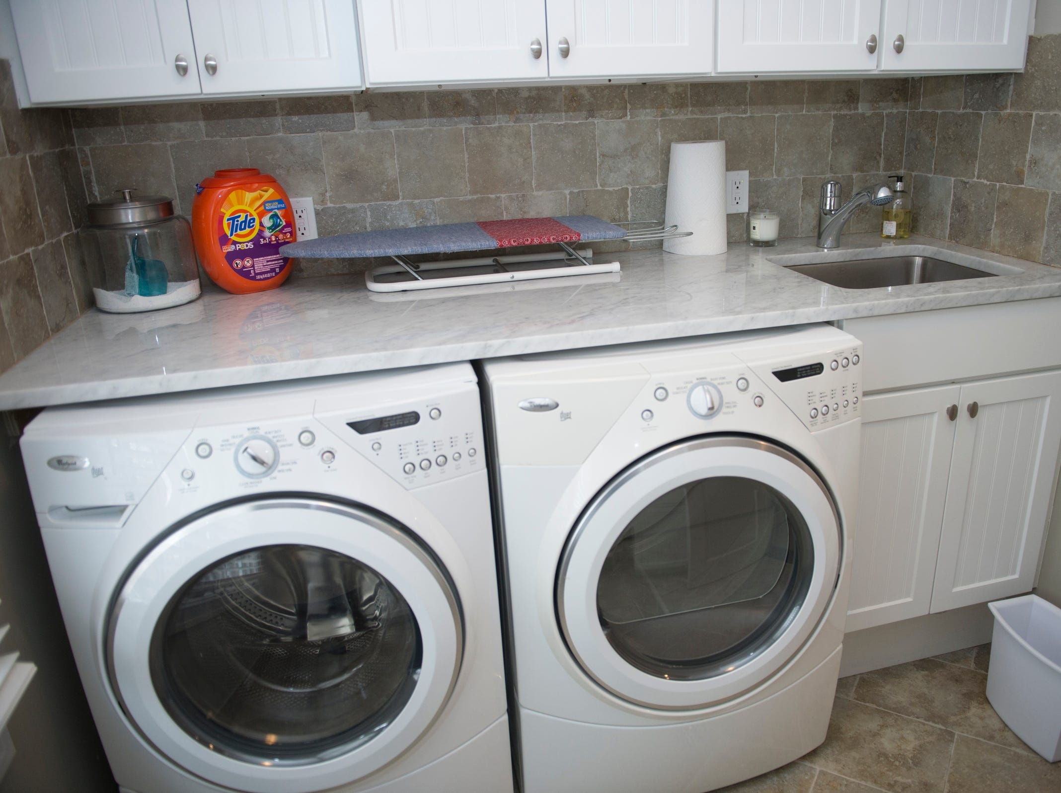 The laundry room includes a washer and drier along with a stone counter.