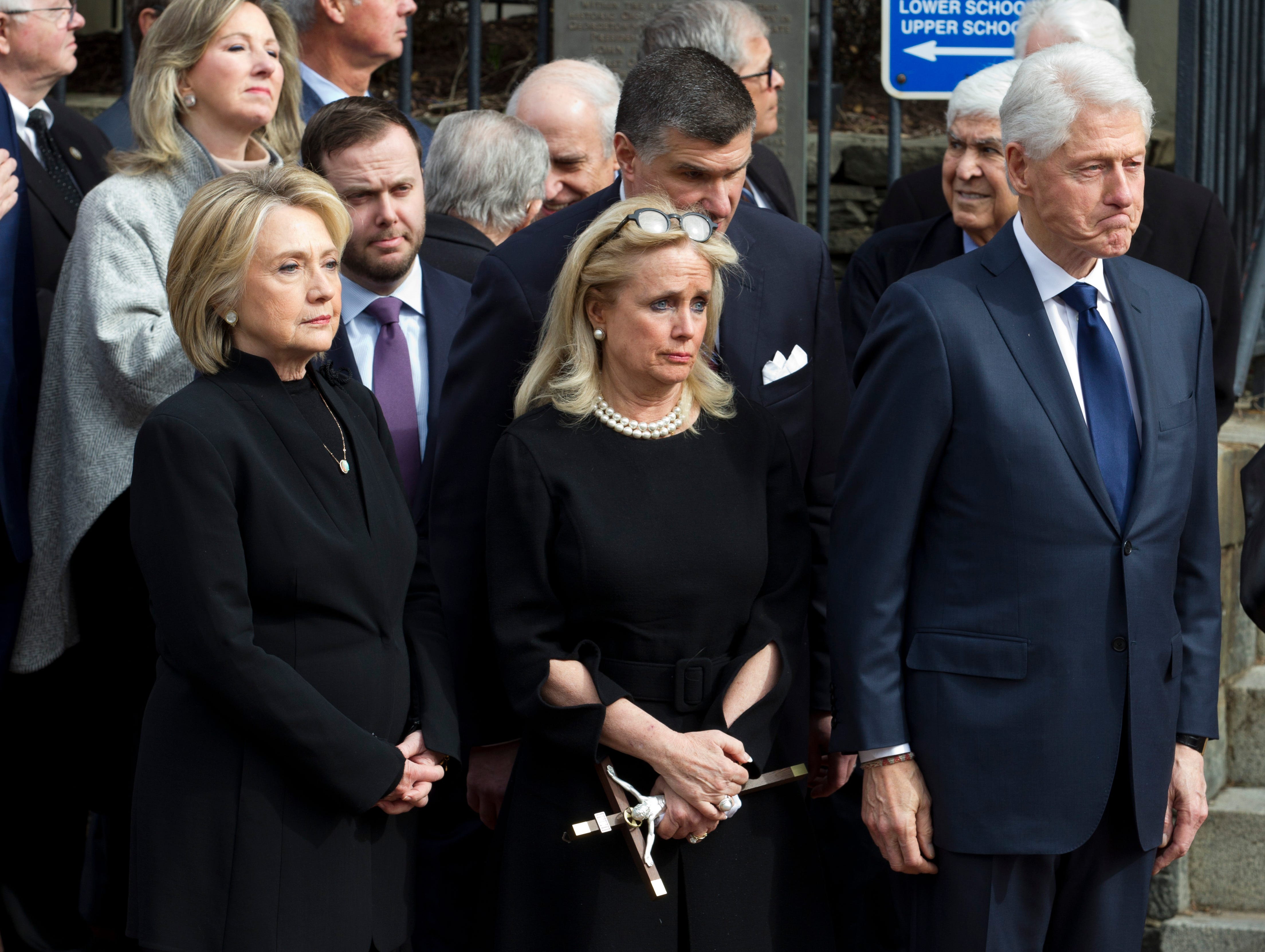 Rep. Debbie Dingell, D-Dearborn, center, accompanied by former President Bill Clinton and former first lady Hillary Clinton, watches the flag-draped casket of former Rep. John Dingell after the funeral at Holy Trinity Catholic Church, Thursday, Feb. 14, 2019, in Washington. Dingell, the longest-serving member of Congress in American history who mastered legislative deal-making and was fiercely protective of Detroit's auto industry, died at age 92.