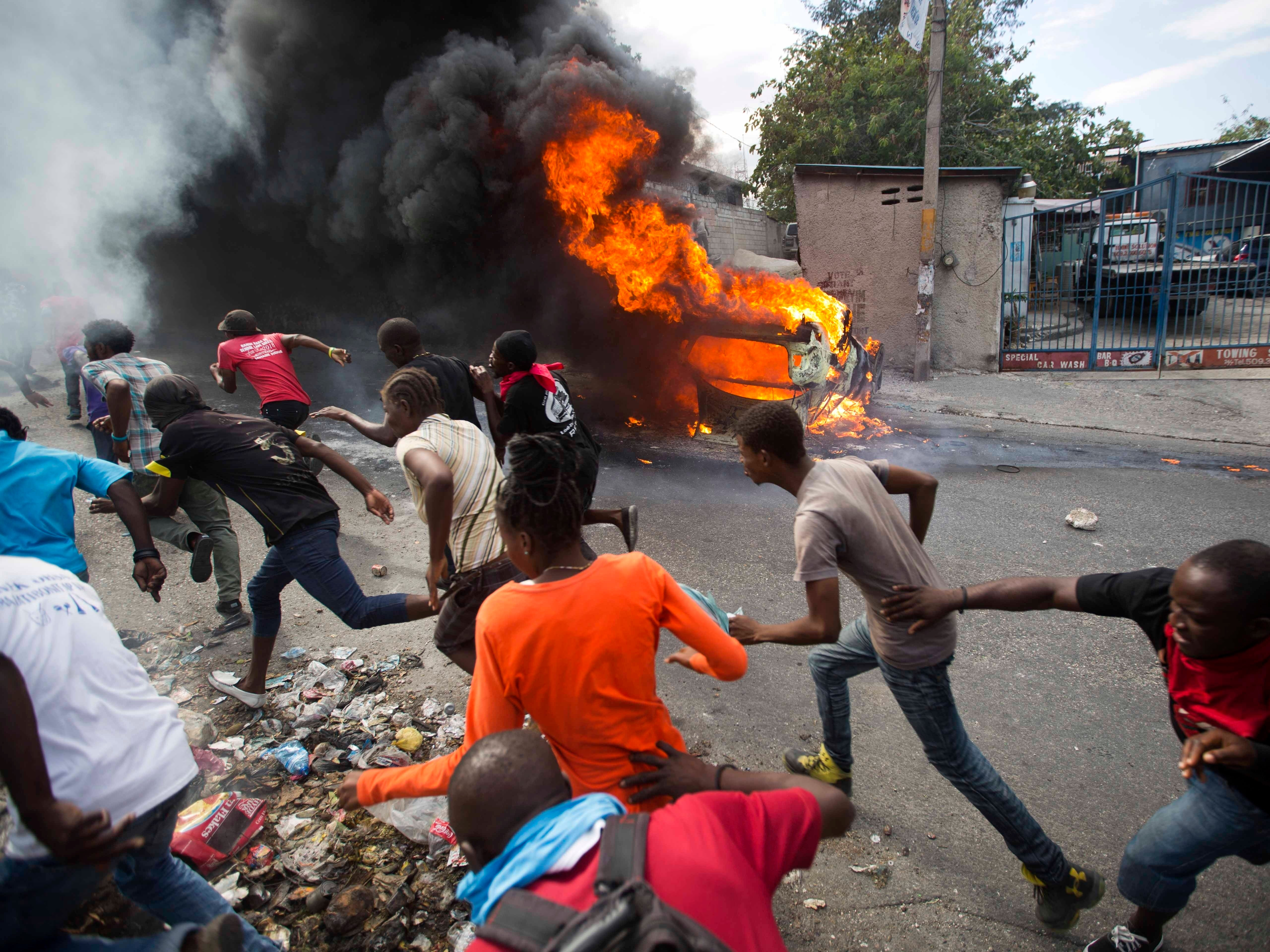 Demonstrators run away from police who are shooting in their direction as a car burns during a protest demanding the resignation of Haitian President Jovenel Moise in Port-au-Prince, Haiti, Tuesday, Feb. 12, 2019. Protesters are angry about skyrocketing inflation and the government's failure to prosecute embezzlement from a multi-billion Venezuelan program that sent discounted oil to Haiti.