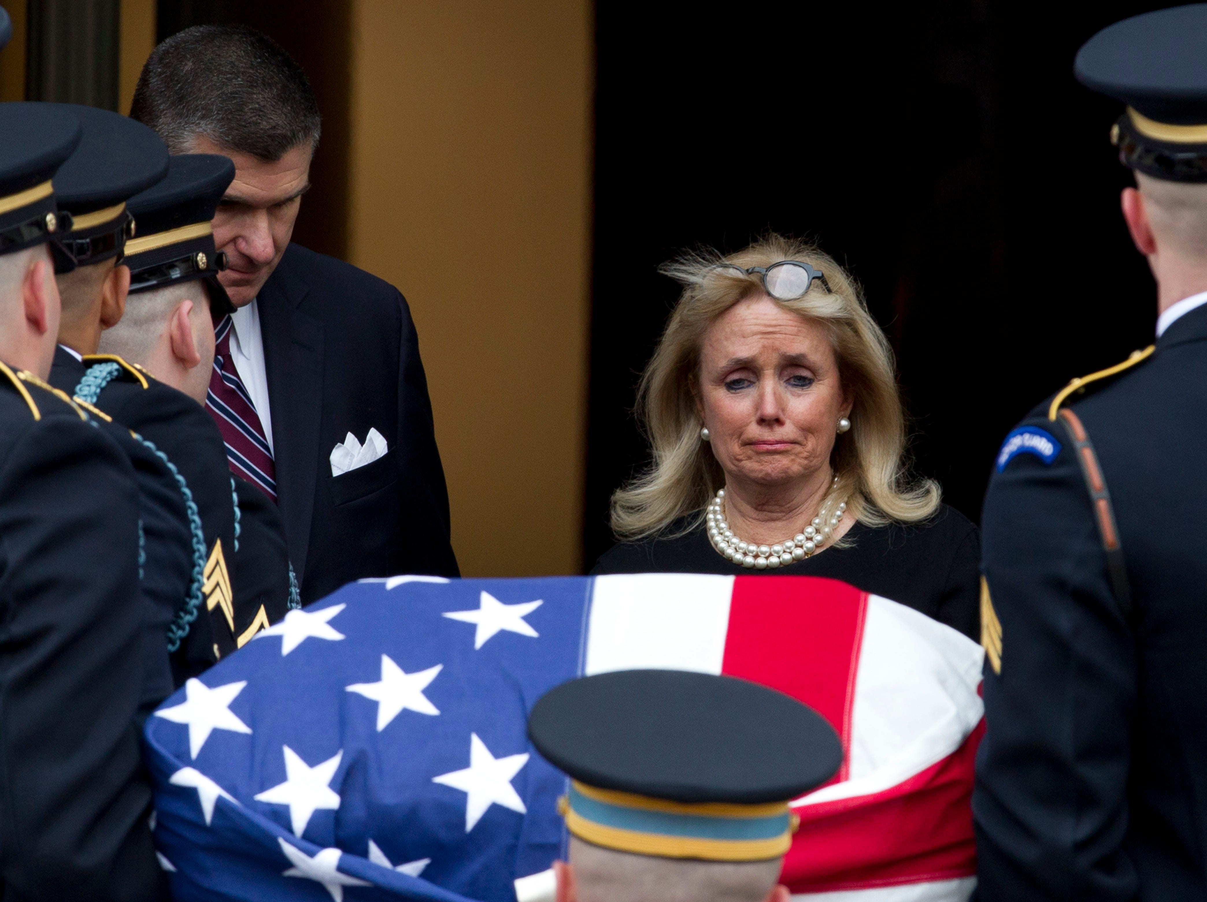 Rep. Debbie Dingell, D-Dearborn, watches the flag-draped casket of her husband,  former Rep. John Dingell, upon arrival at Holy Trinity Catholic Church for his funeral Thursday.