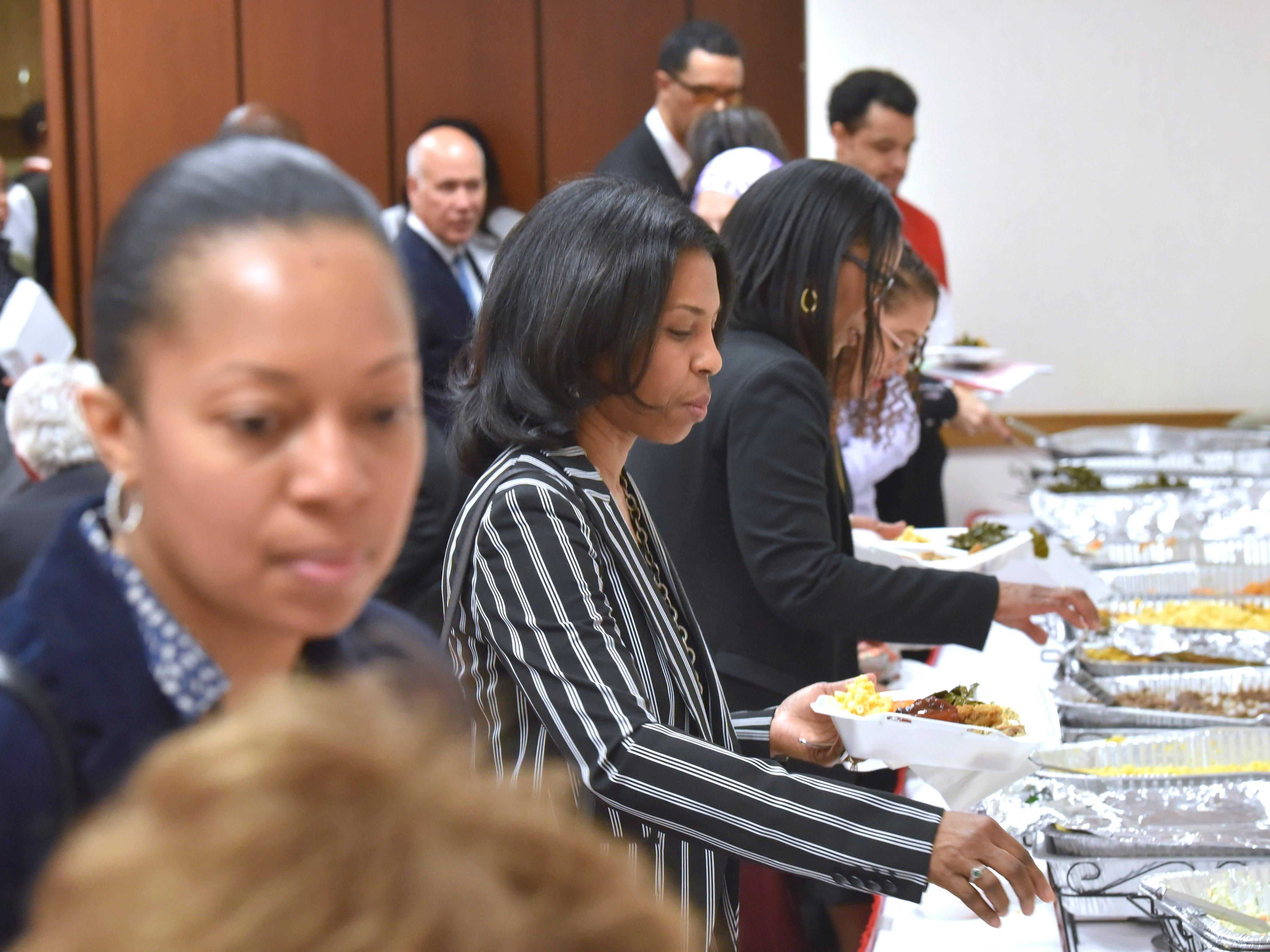 Bonita Gardner, center, former court clerk for Judge Keith, serves herself soul food.