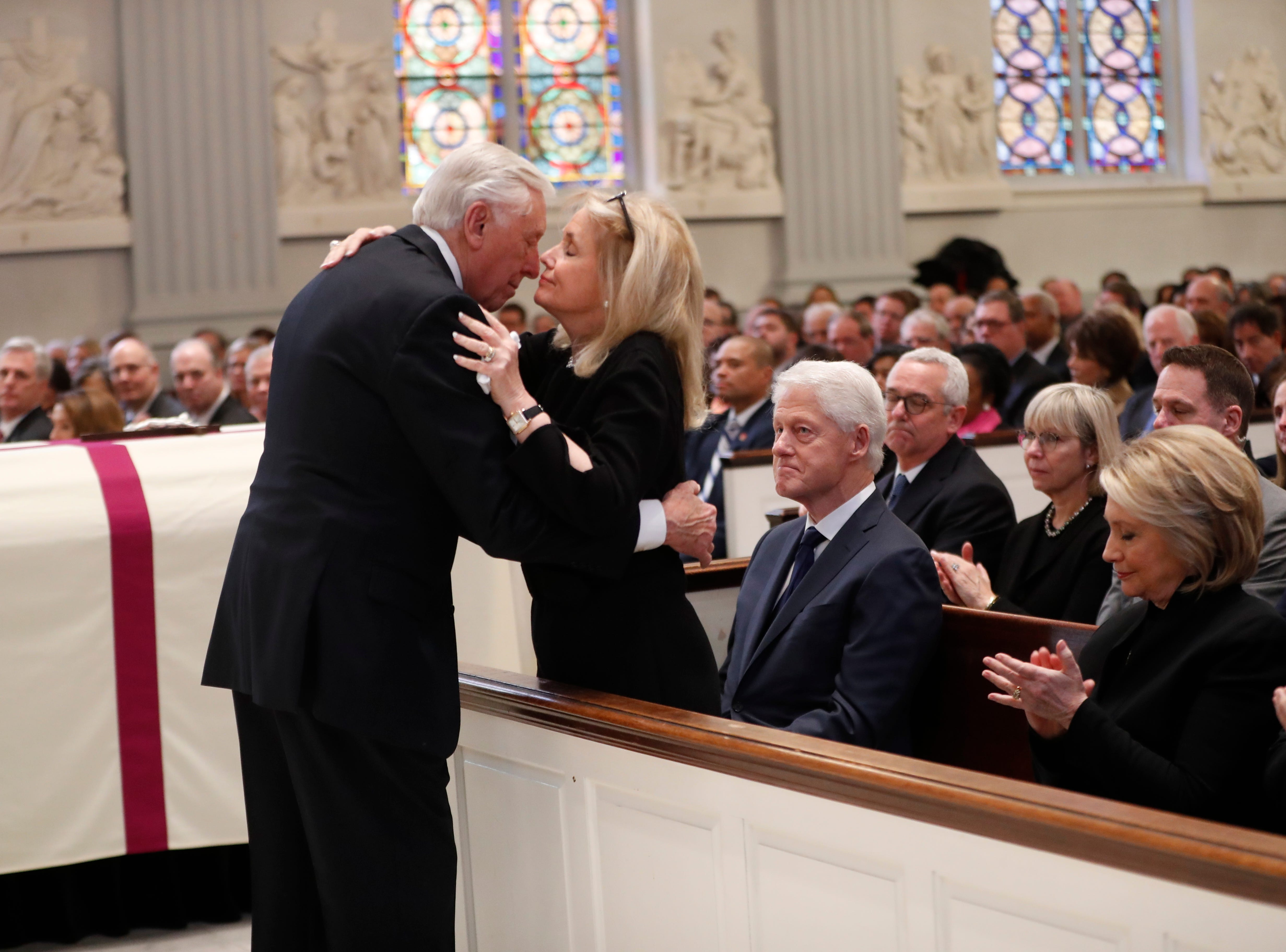 Rep. Steny Hoyer, D-Md., hugs Rep. Debbie Dingell, D-Dearborn, during the funeral for her husband, former Rep. John Dingell.