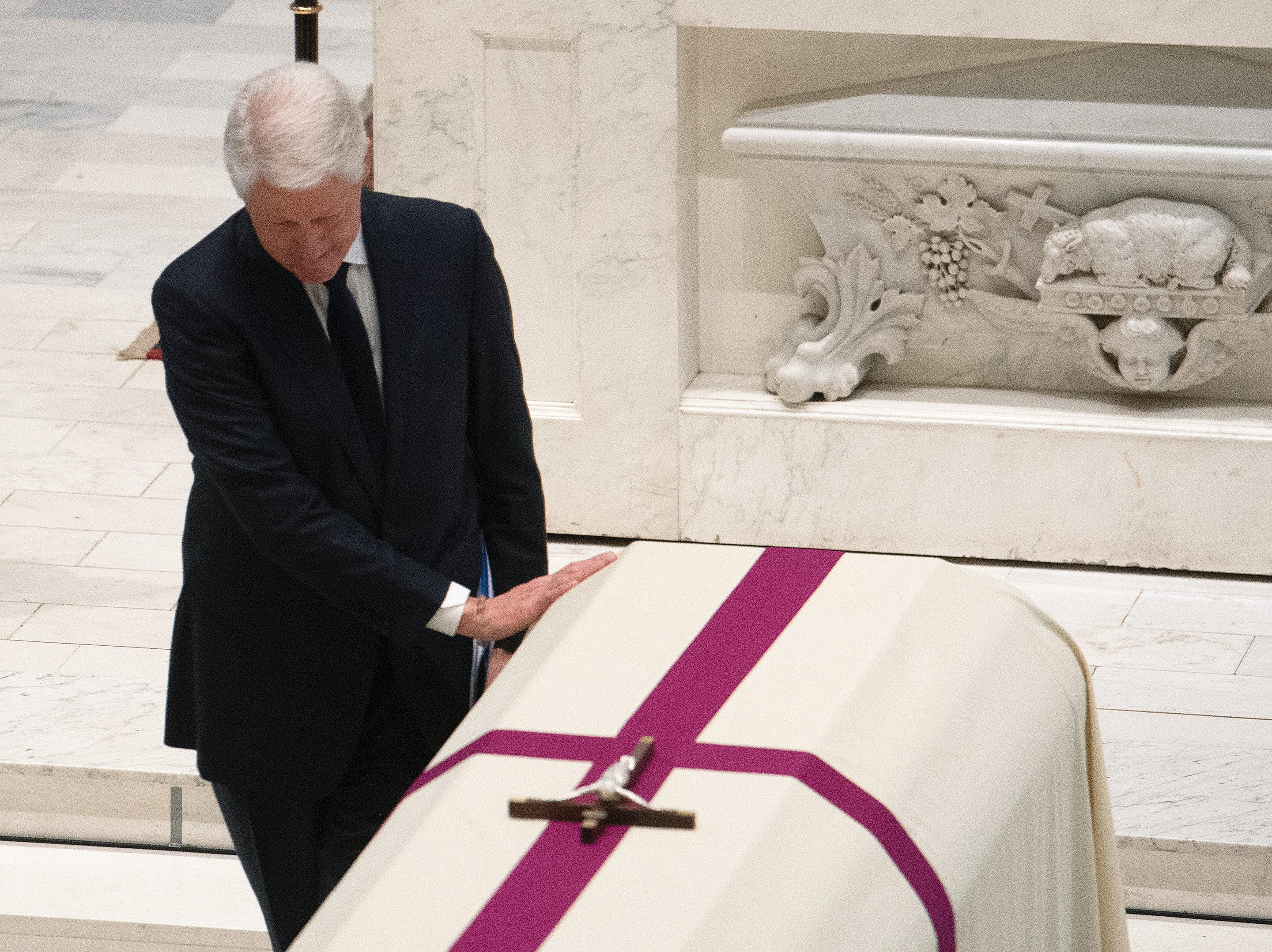 Former President Bill Clinton touches the casket of former Rep. John Dingell, D-Dearborn, after addressing the funeral at the Holy Trinity Catholic Church in Washington.