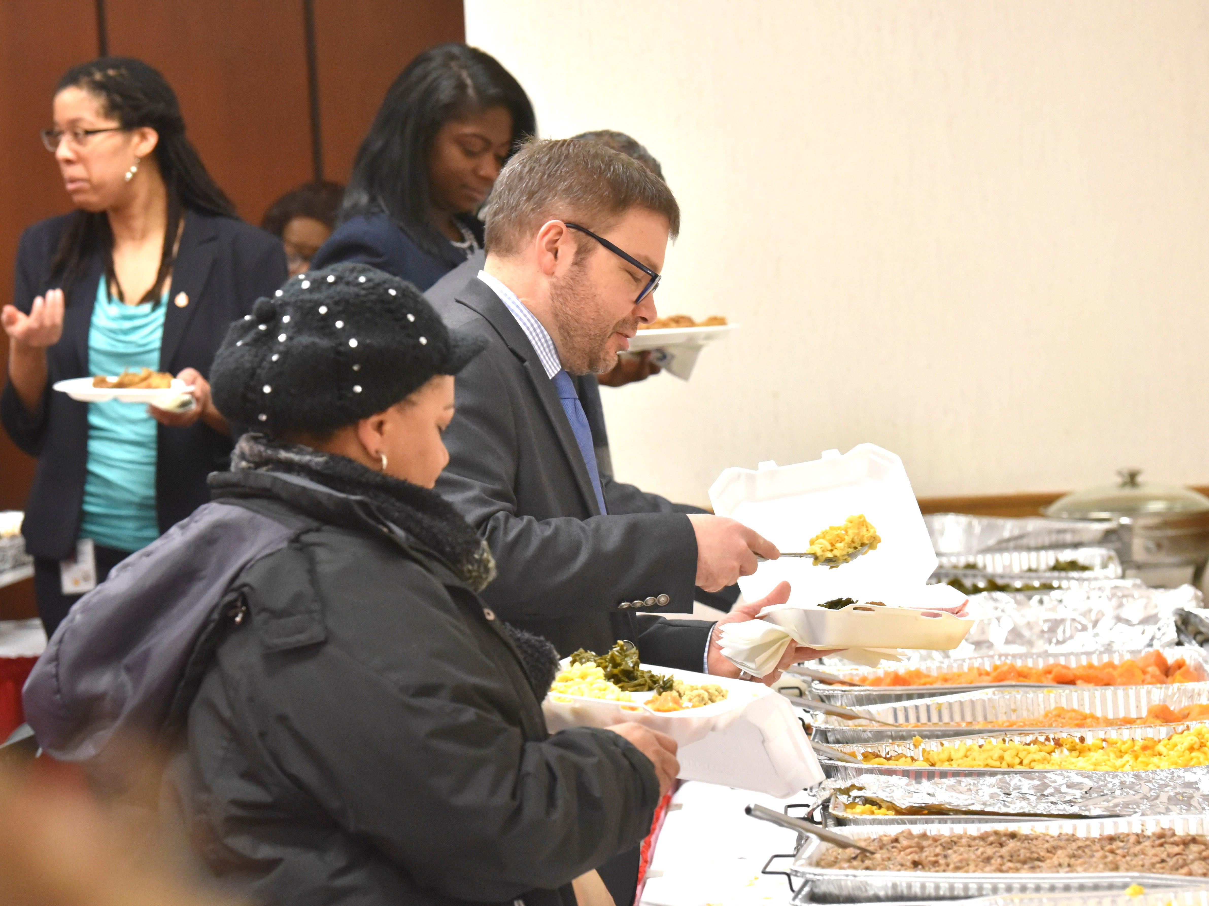 U.S. District Court Magistrate Judge Anthony P. Patti, center, serves himself soul food.