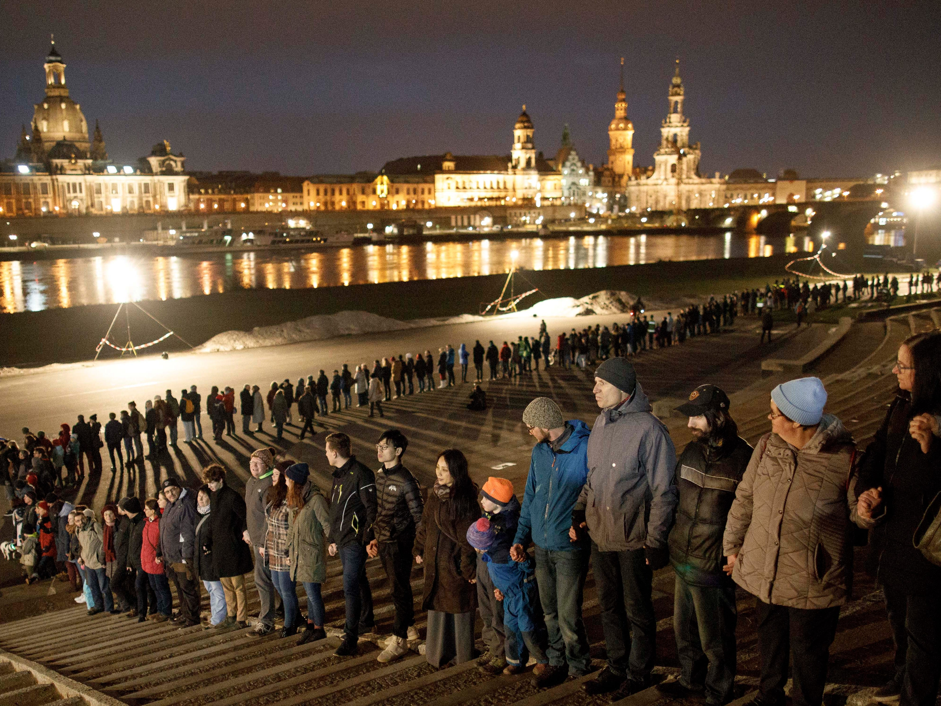 People hold hands in a human chain to commemorate the 74th anniversary of the firebombing of the city during World War II on Feb. 13, 2019 in Dresden, Germany. From Feb. 13-15, 1945, U.S. and British bombers firebombed the city center, killing an estimated 25,000 people.