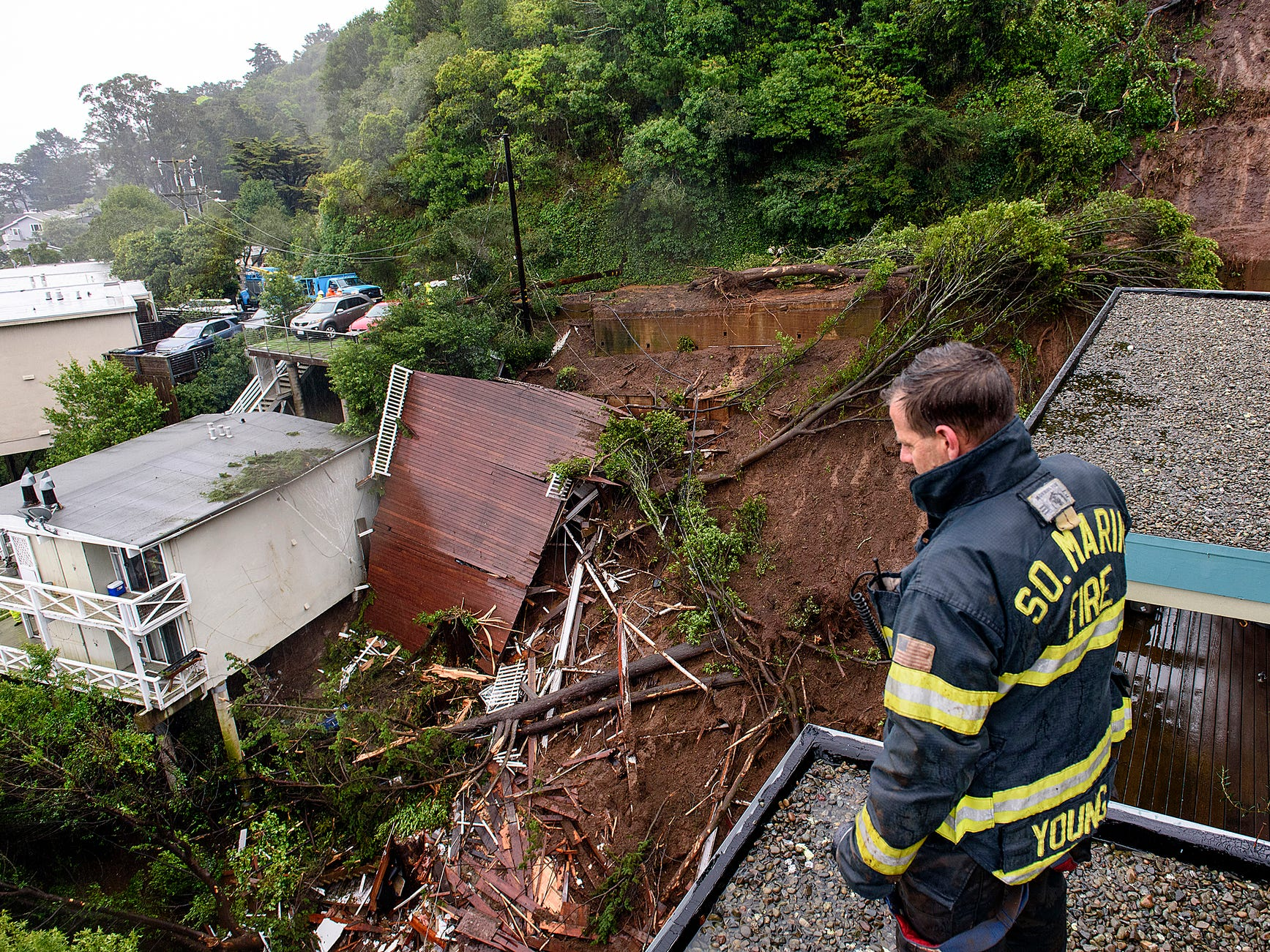 Firefighter/paramedic Patrick Young with the Southern Marin Fire Department looks out over the aftermath of a mudslide that destroyed three homes on a hillside in Sausalito, Calif., Thursday, Feb. 14, 2019. The National Weather Service says the atmospheric river sagged southward from Northern California overnight and is pointed at the southwestern corner of the state early Thursday.