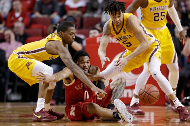 Minnesota's Dupree McBrayer, left, Amir Coffey (5) and Nebraska's James Palmer Jr. (0) go for a loose ball.