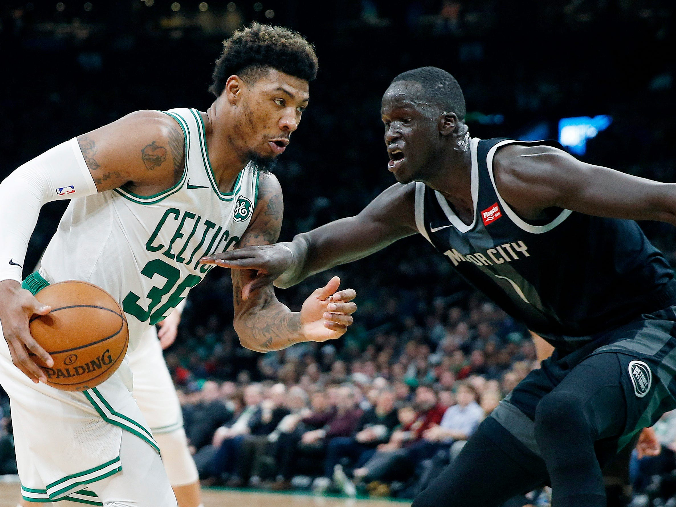 Boston Celtics' Marcus Smart, left, drives for the basket against Detroit Pistons' Thon Maker, right, during the first half.