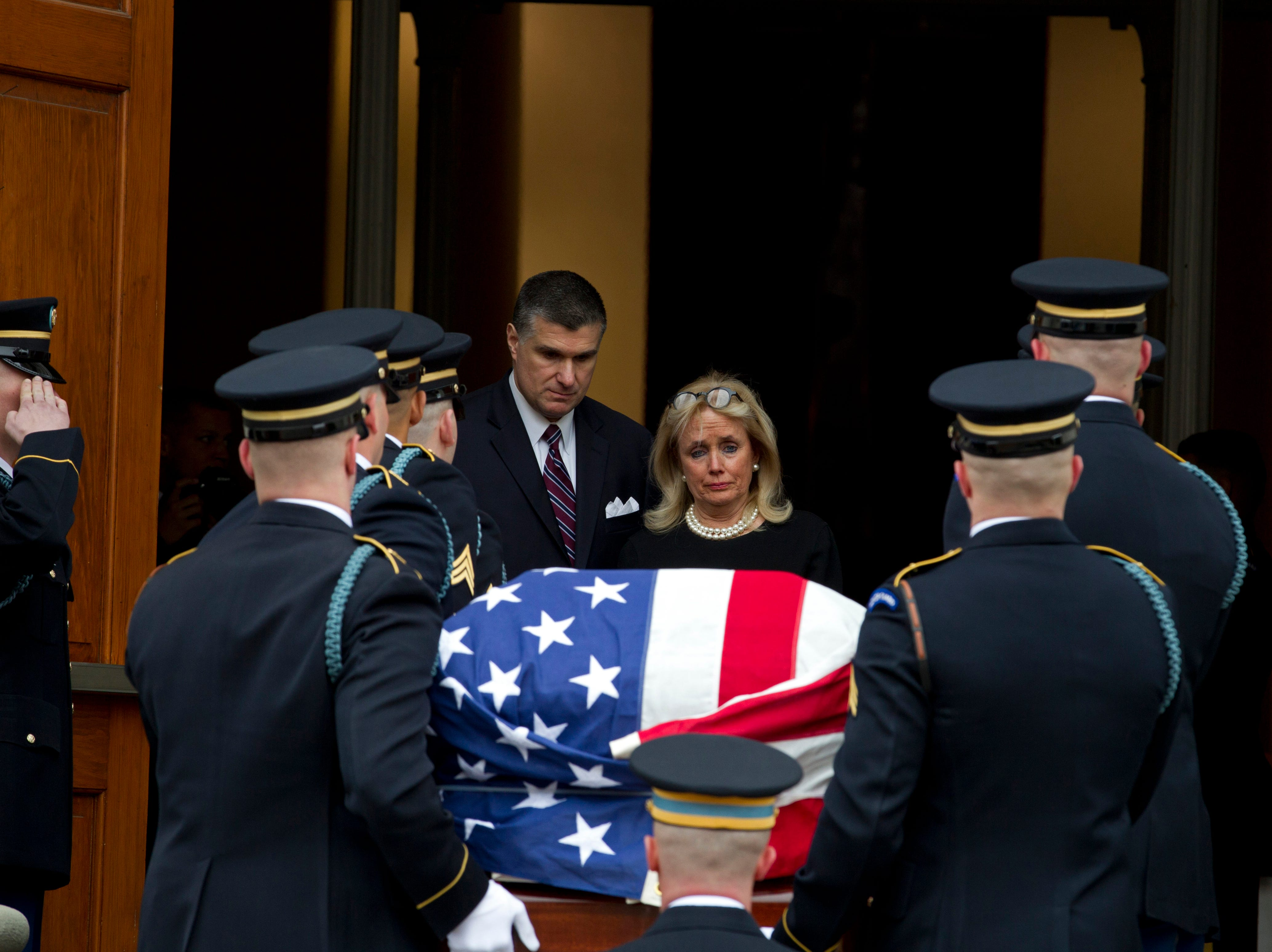Rep. Debbie Dingell, D-Mich., watches the flag-draped casket of former Rep. John Dingell upon arrival at Holy Trinity Catholic Church.