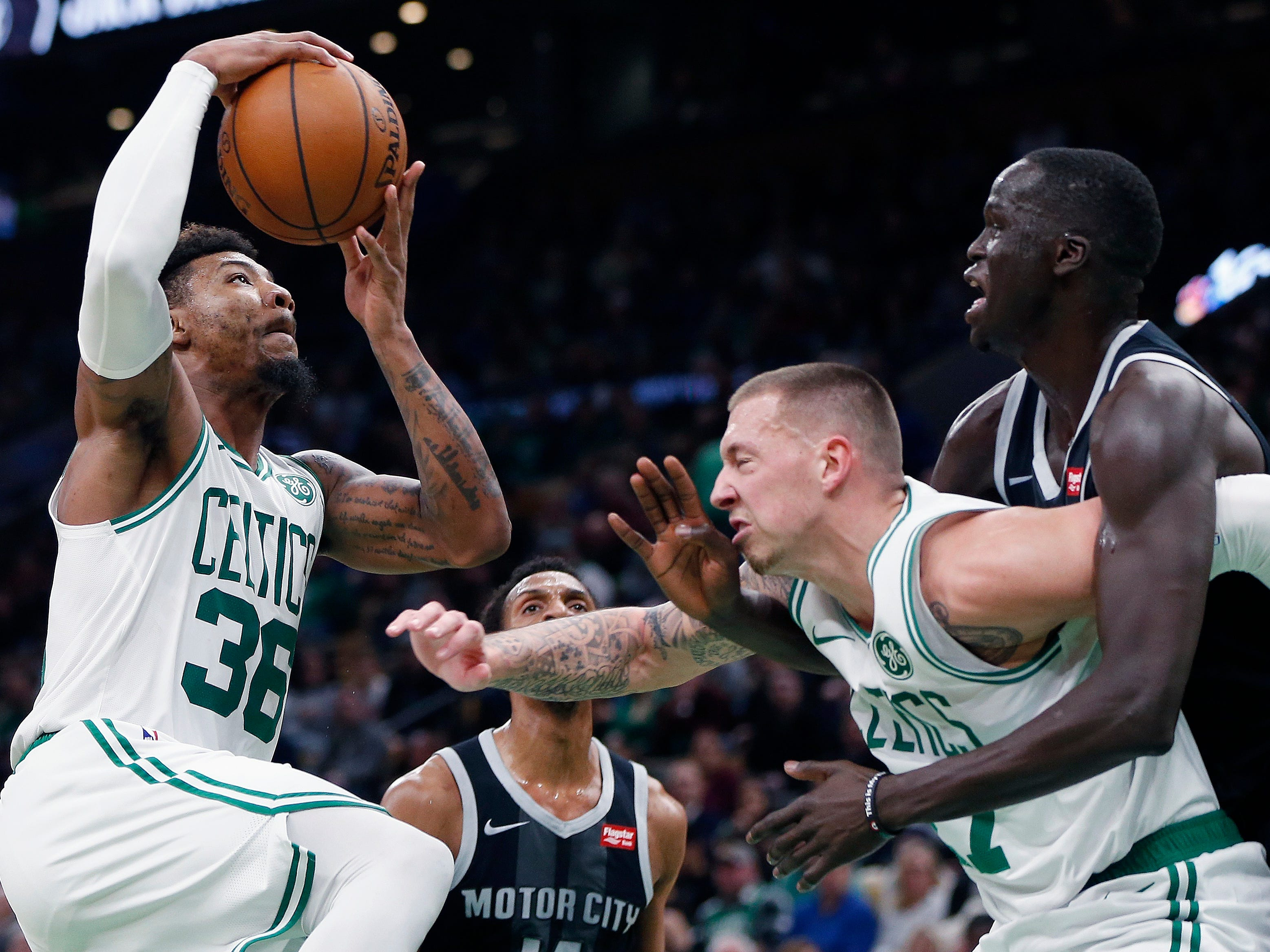 Boston Celtics' Marcus Smart, left, goes up to shoot as Daniel Theis, center, screens Detroit Pistons' Thon Maker, right, during the first half.