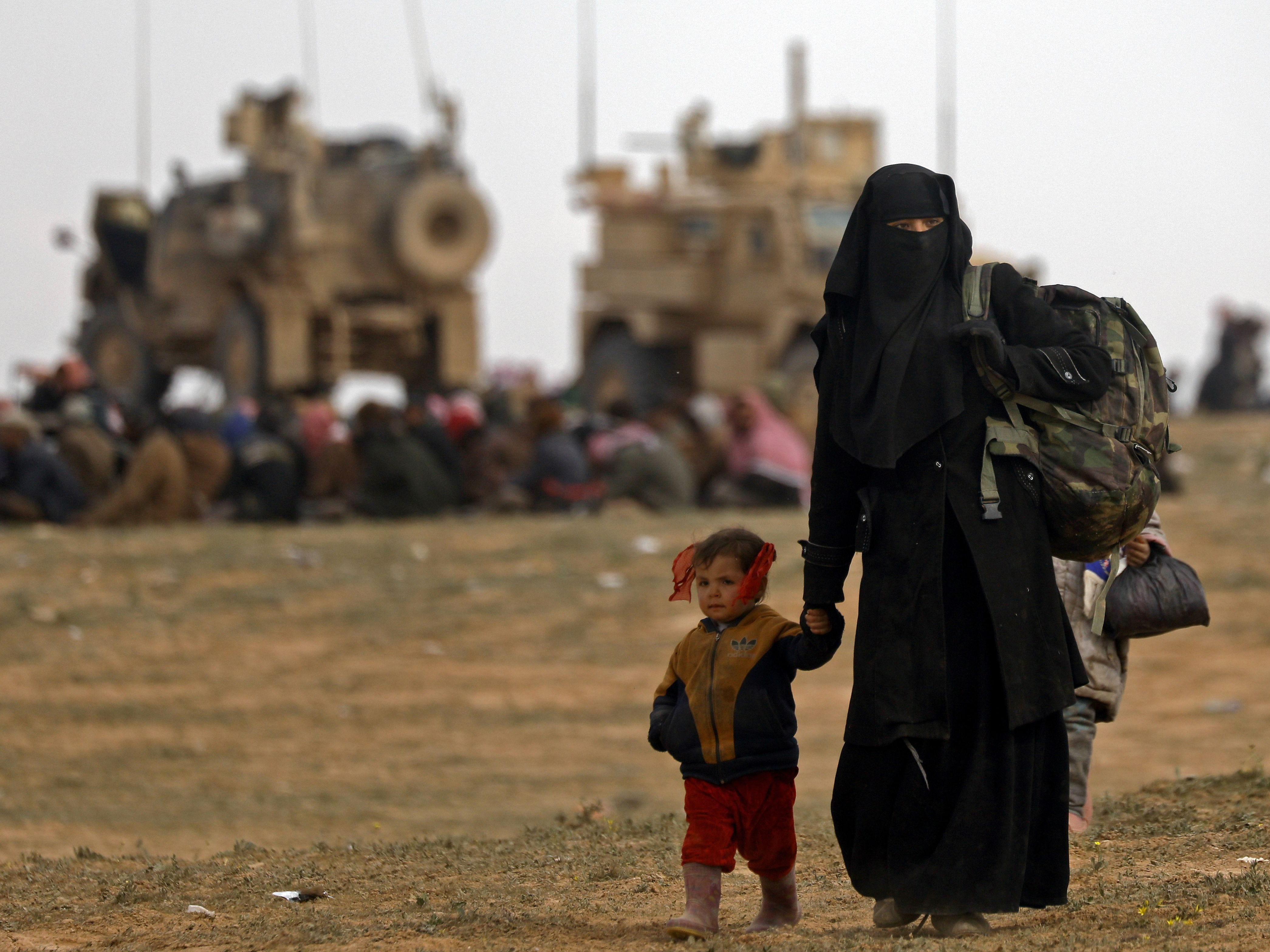 """Civilians fleeing the Islamic State's group embattled holdout of Baghouz walk in a field on Feb. 13, 2019 during an operation by the US-backed Syrian Democratic Forces (SDF) to expel the Islamic State group from the area, in the eastern Syrian province of Deir Ezzor. Syrian fighters backed by artillery fire from a US-led coalition battled a fierce jihadist counteroffensive as they pushed to retake a last morsel of territory from the Islamic State group in an assault lasting days. More than four years after the extremists declared a """"caliphate"""" across large parts of Syria and neighboring Iraq, several offensives have whittled that down to a tiny scrap of land in eastern Syria."""