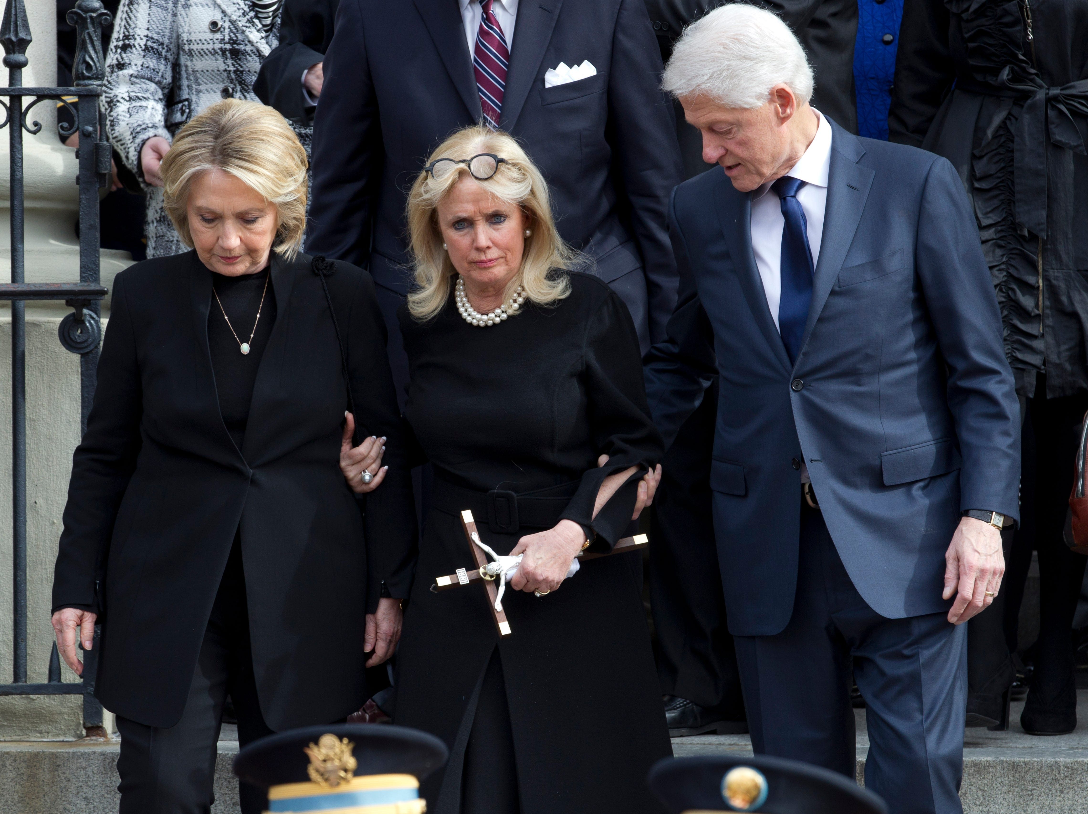 Rep. Debbie Dingell, D-Dearborn, center, accompanied by former President Bill Clinton and former first lady Hillary Clinton, follows the flag-draped casket of former Rep. John Dingell after his funeral at Holy Trinity Catholic Church, Thursday, Feb. 14, 2019, in Washington.
