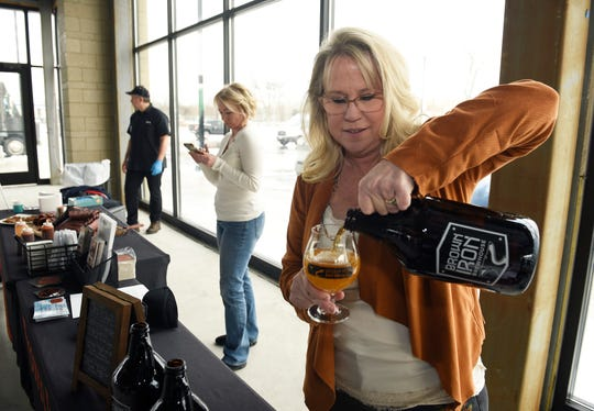 Patti Eisenbraun, Co-owner of Brown Iron Brewhouse in Washington Township, pours a glass of beer during the press event. Brown Iron Brewhouse will be one of the new retailers in the Woodward Corners by Beaumont development.