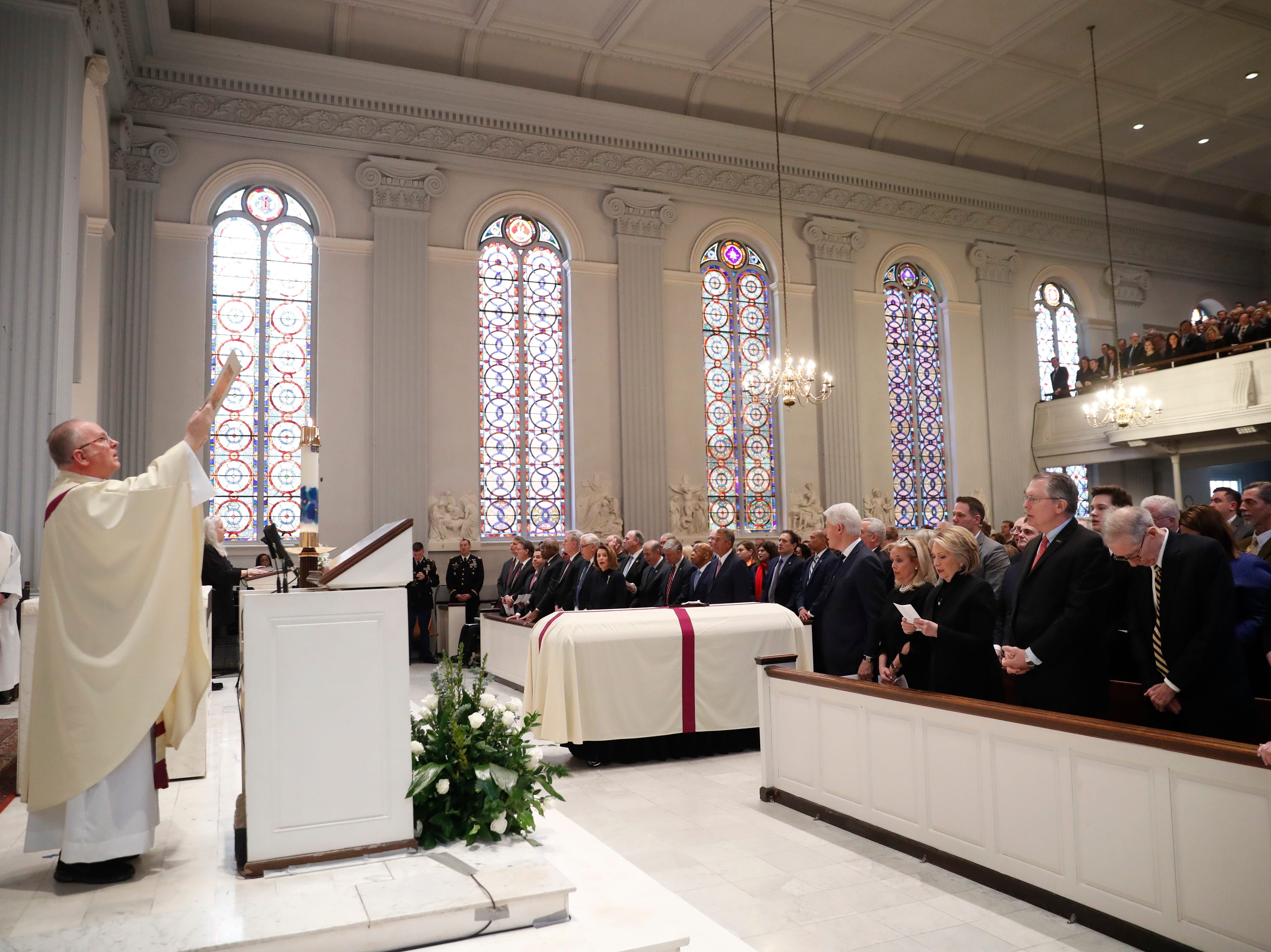 Rev. Patrick Conroy holds up a Bible during the homily at the funeral for former Rep. John Dingell.