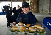 Veronica Rallo, 30, a employee for Wahlburgers, serves burgers during the Woodward Corners by Beaumont development press conference .