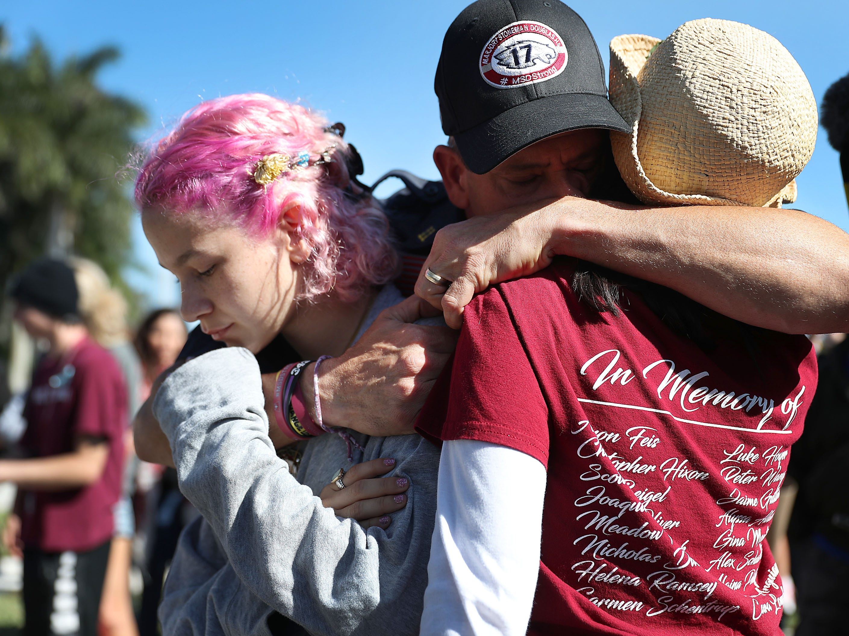 Anthony Gonzalez hugs his daughter, Victoria Gonzalez, and her teacher Ronit Reoven as they visit a memorial set up near Marjory Stoneman Douglas High School, where 14 students and three staff members were killed in a mass shooting a year ago in Parkland, Florida. Gonzalez is a captain at the Coral Springs Fire Department and responded to the shooting a year ago.